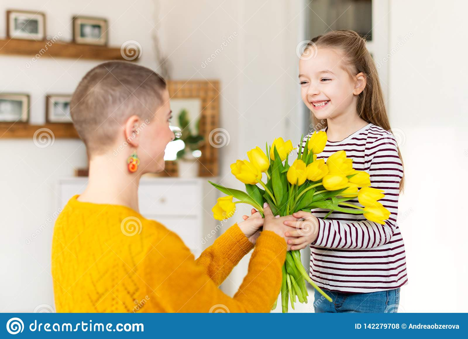 Szczęśliwy matka urodziny lub dnia tło Urocza młoda dziewczyna zaskakuje jej mamy z bukietem tulipany Rodzinny świętowanie