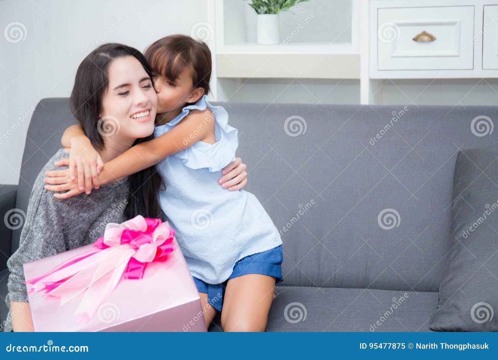 Szczęśliwy matki, córki azjata z prezentem z różową buziak matką i