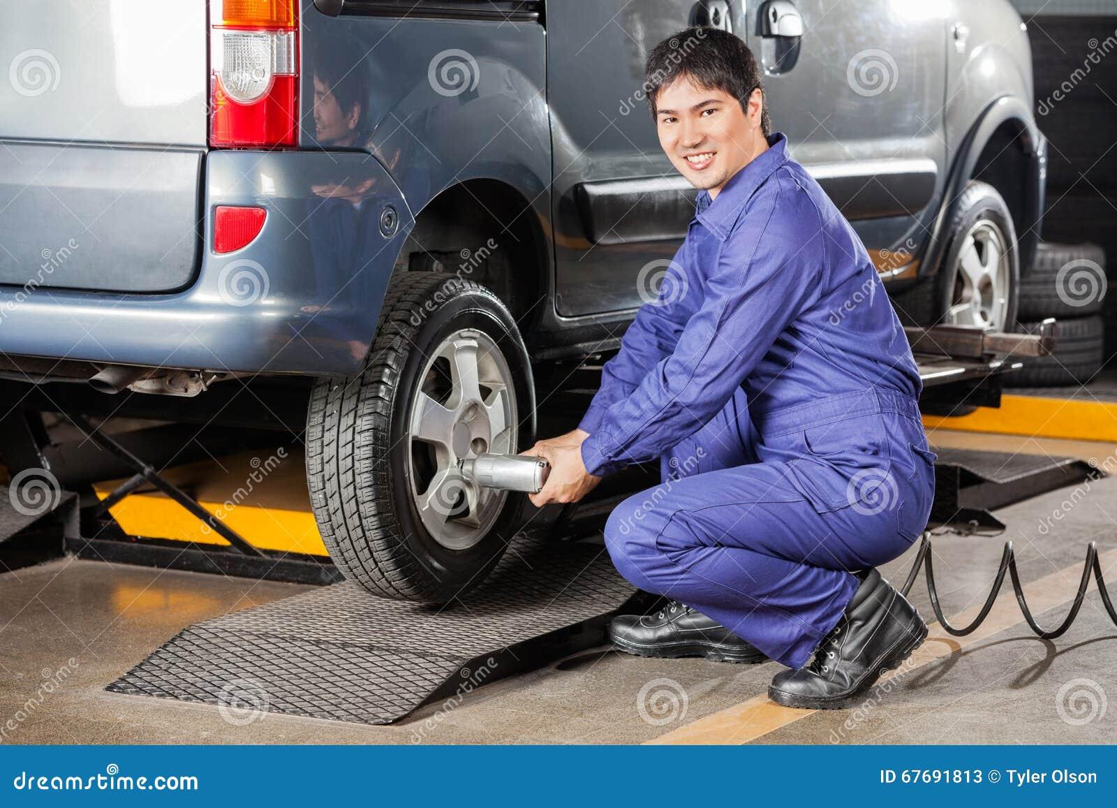 Szczęśliwy mechanik Załatwia Samochodową oponę Przy Remontowym sklepem