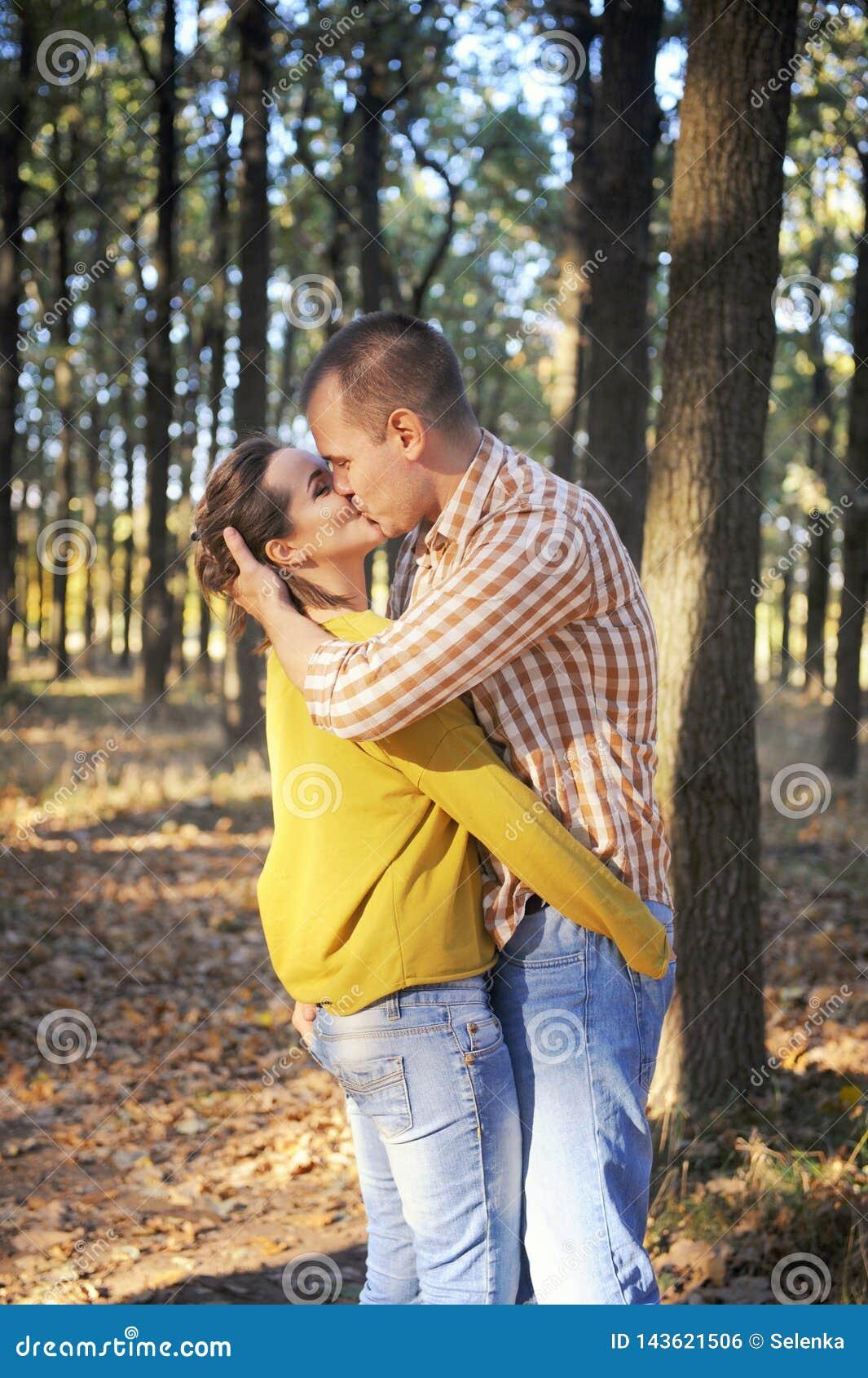 Szczęśliwy miłości pary odprowadzenie w lesie i całowaniu, młoda dorosła romantyczna para, przypadkowa odzież