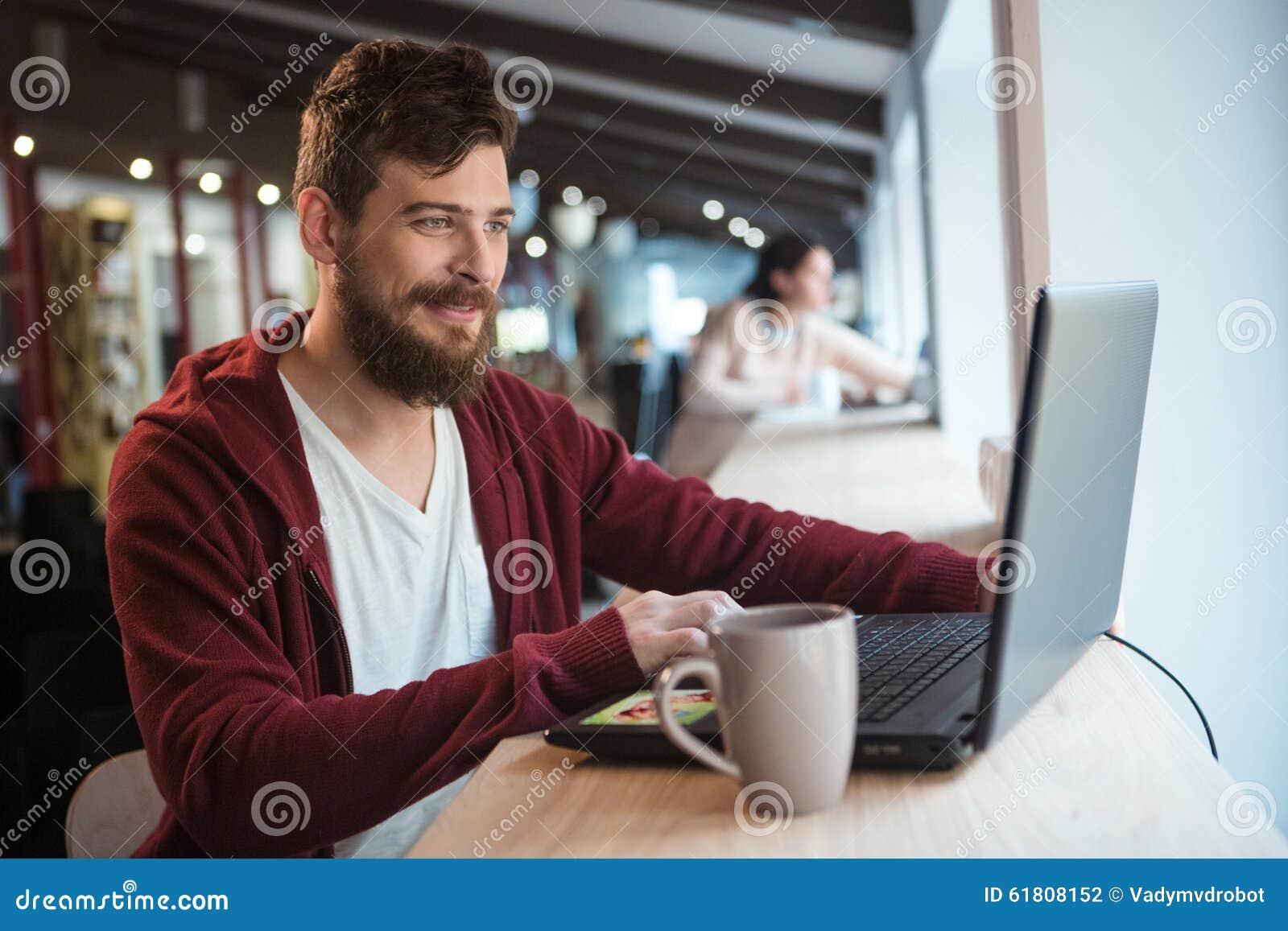 Szczęśliwy modniś pracuje w biurowym używa laptopie