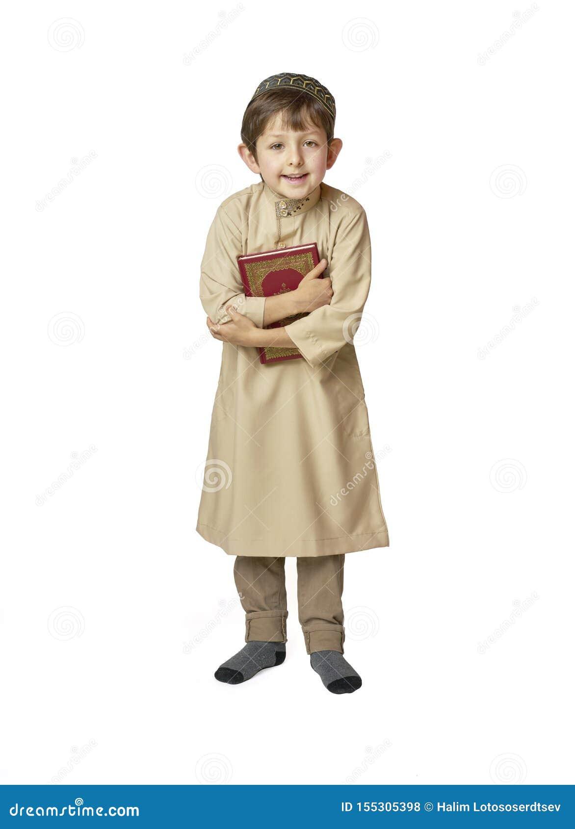 Szczęśliwy muzułmański dzieciak trzyma świętego koran na białym tle