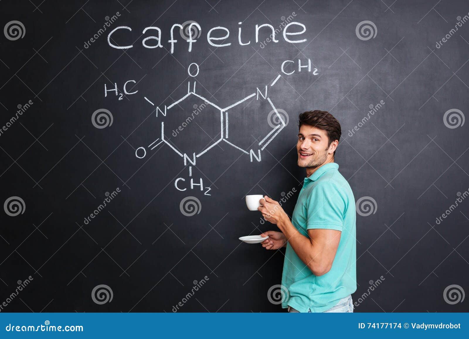 Szczęśliwy naukowiec pije kawę nad chemiczną strukturą kofeiny molekuła