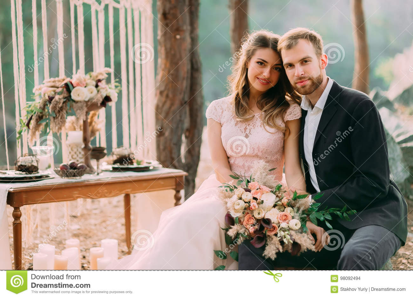 Szczęśliwy nowożeńcy spojrzenie na fotografie Mężczyzna i kobieta w świątecznych ubraniach siedzimy na kamieniach blisko ślubnej
