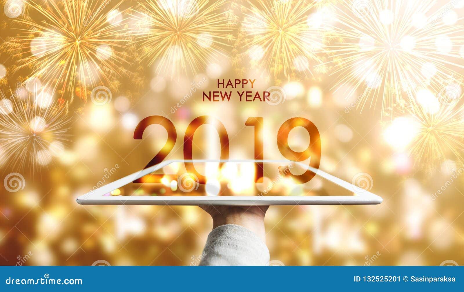 Szczęśliwy nowy rok 2019, ręka trzyma cyfrową pastylkę z luksusowym złocistym Bokeh fajerwerków tłem
