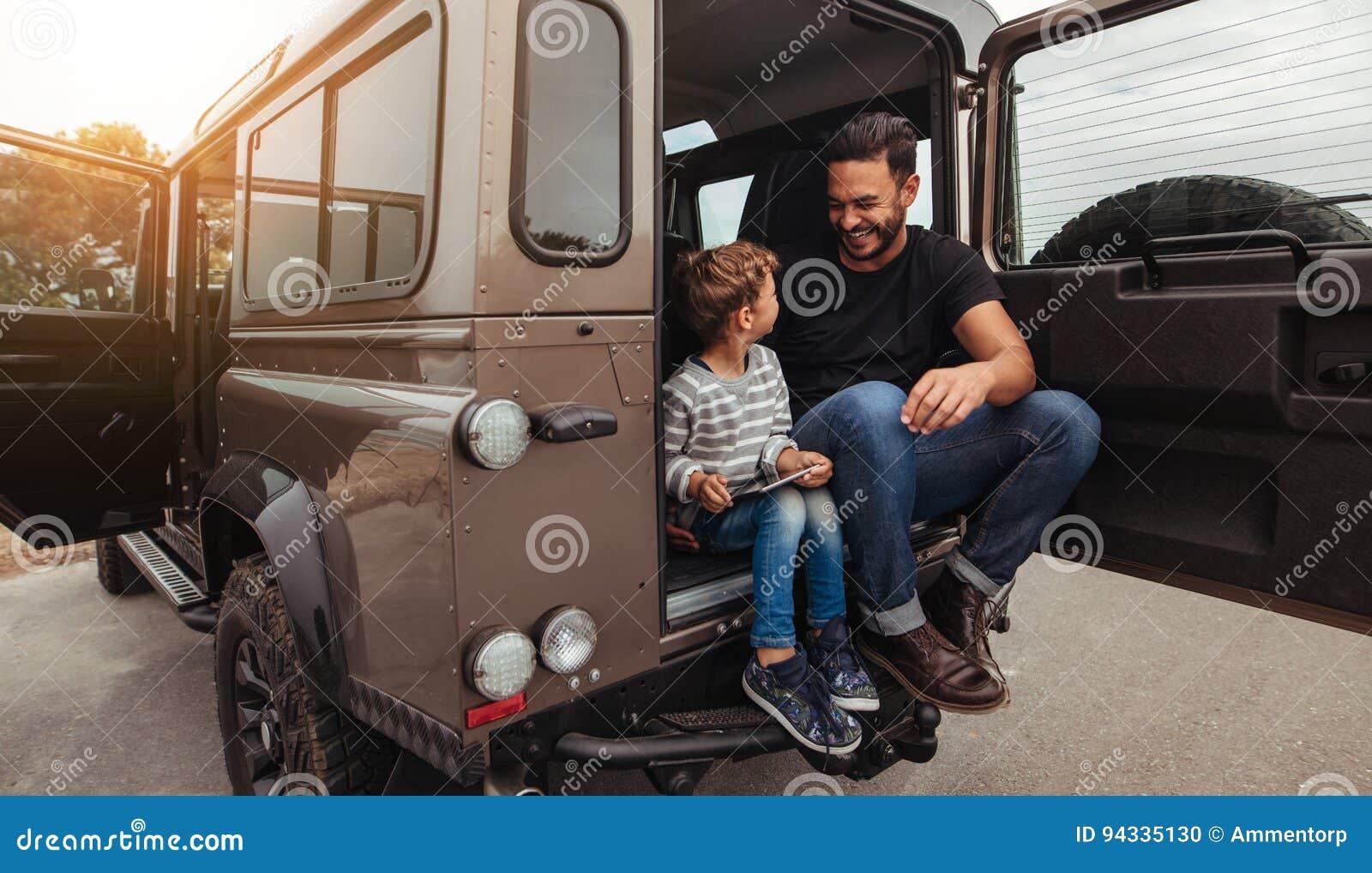 Szczęśliwy ojca i syna obsiadanie przy plecy samochód