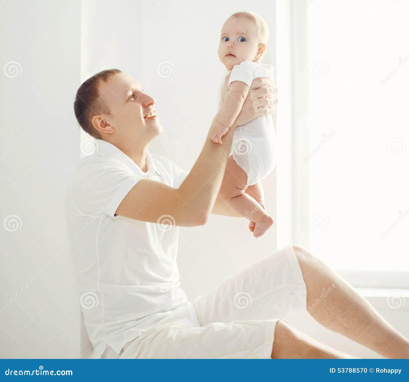 Szczęśliwy ojciec trzyma dalej wręcza jego dziecka w białym pokoju w domu