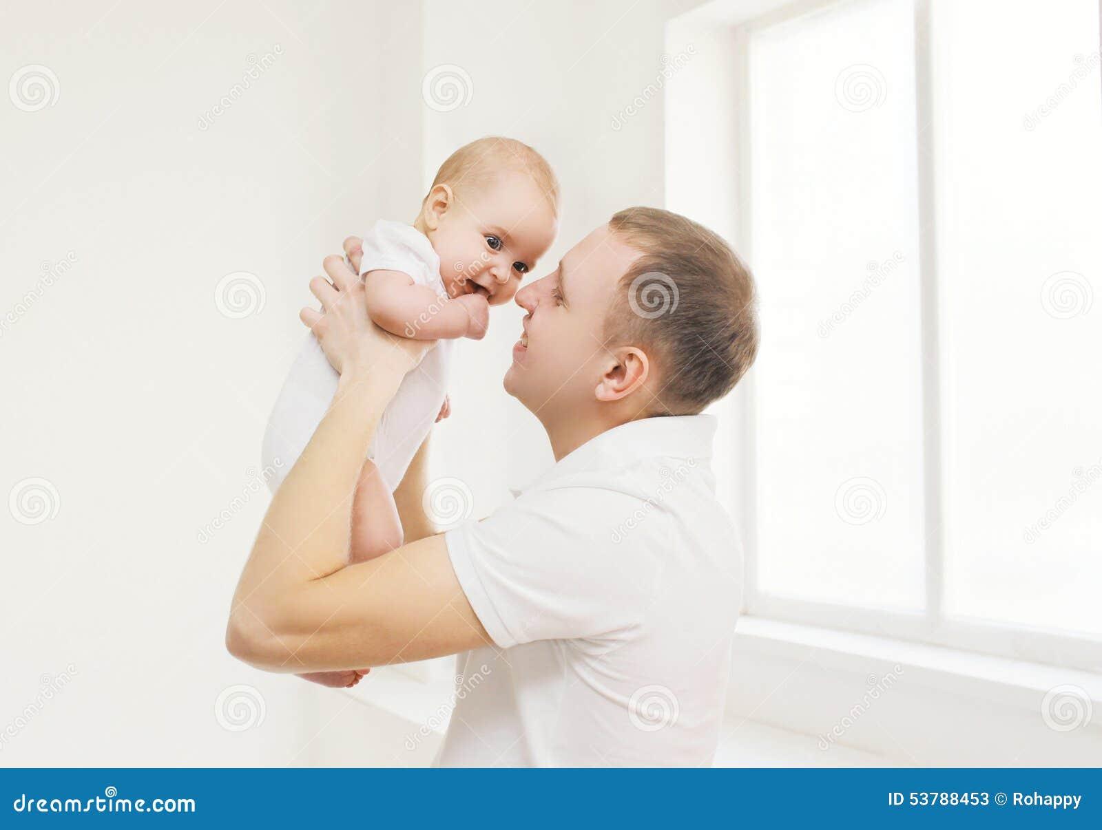 Szczęśliwy ojciec trzyma dalej wręcza jego dziecka w domu