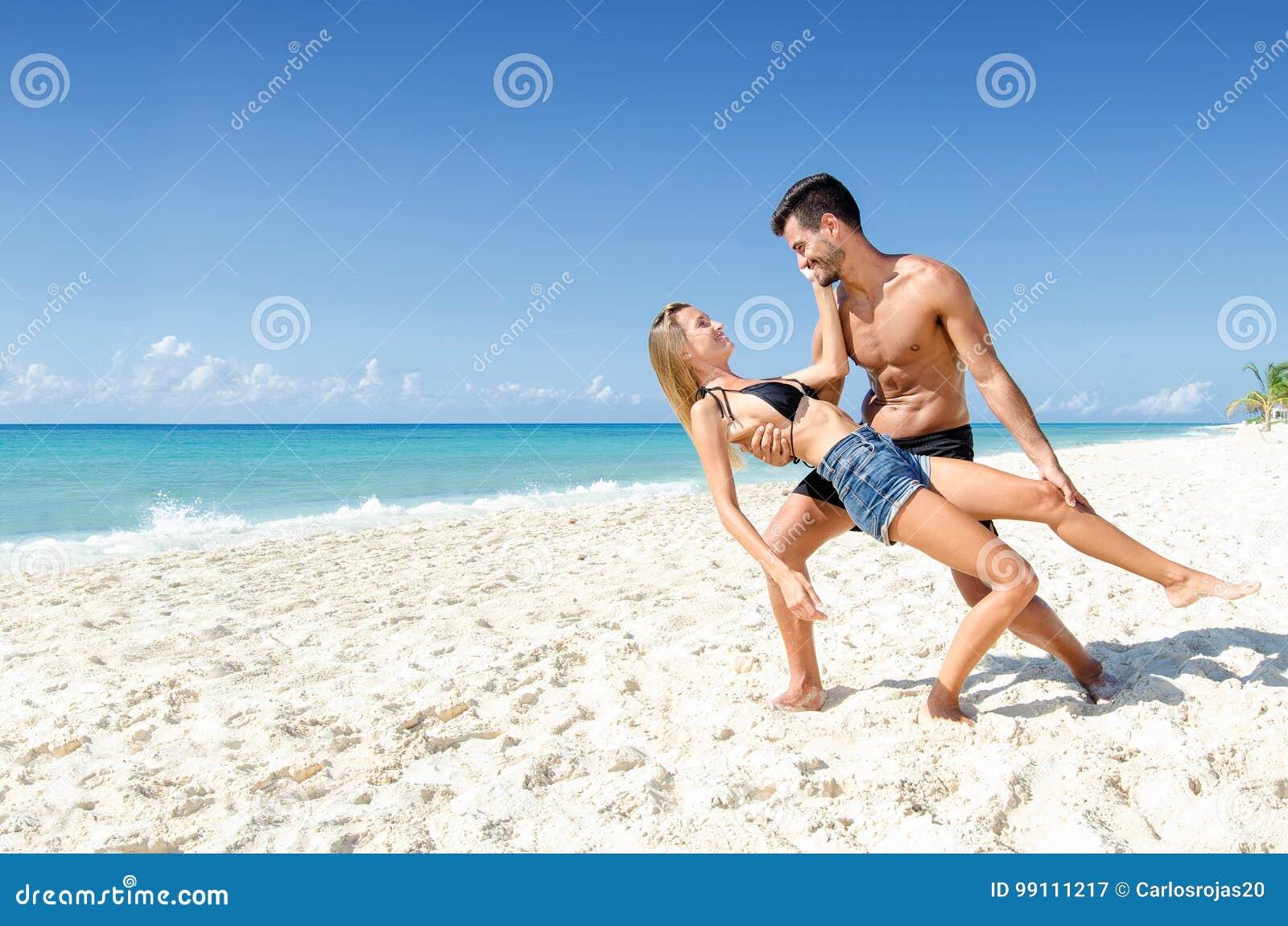 Szczęśliwy para taniec z miłością przy plażą