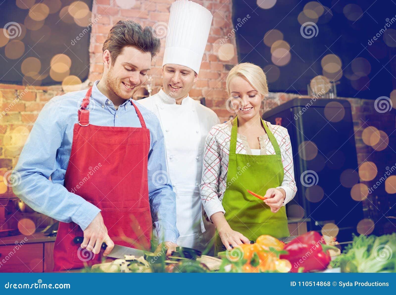 Szczęśliwy pary i samiec szef kuchni gotuje kucharstwo w kuchni
