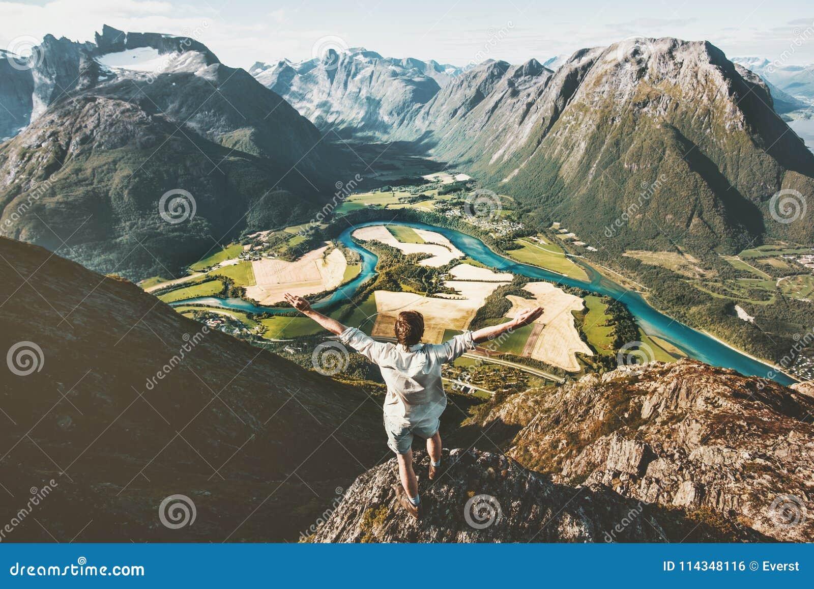 Szczęśliwy podróżnika mężczyzna podnoszący zbroi pozycję na falezie nad górami
