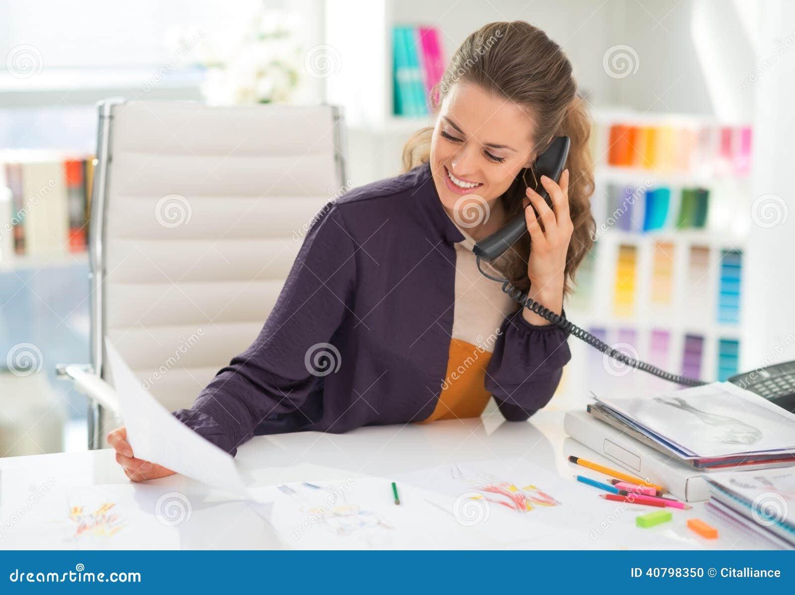 Szczęśliwy projektant mody w biurowym opowiada telefonie