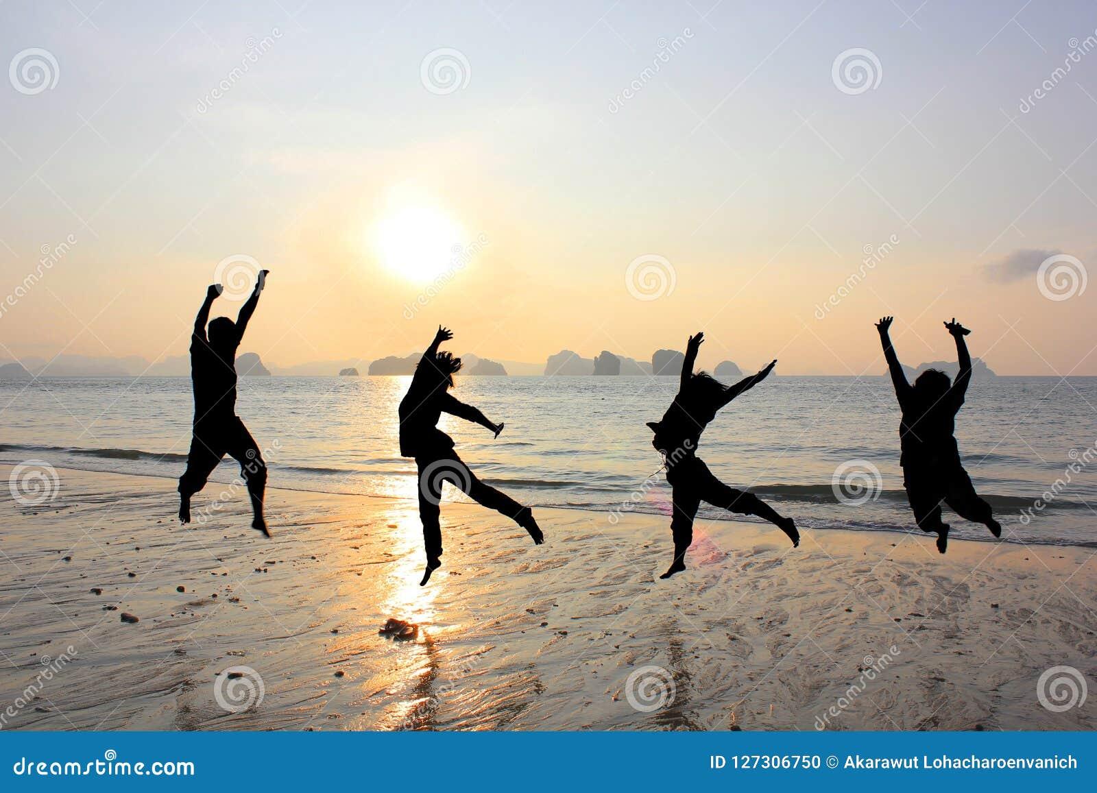 Szczęśliwy przyjaźni doskakiwanie przy plażą