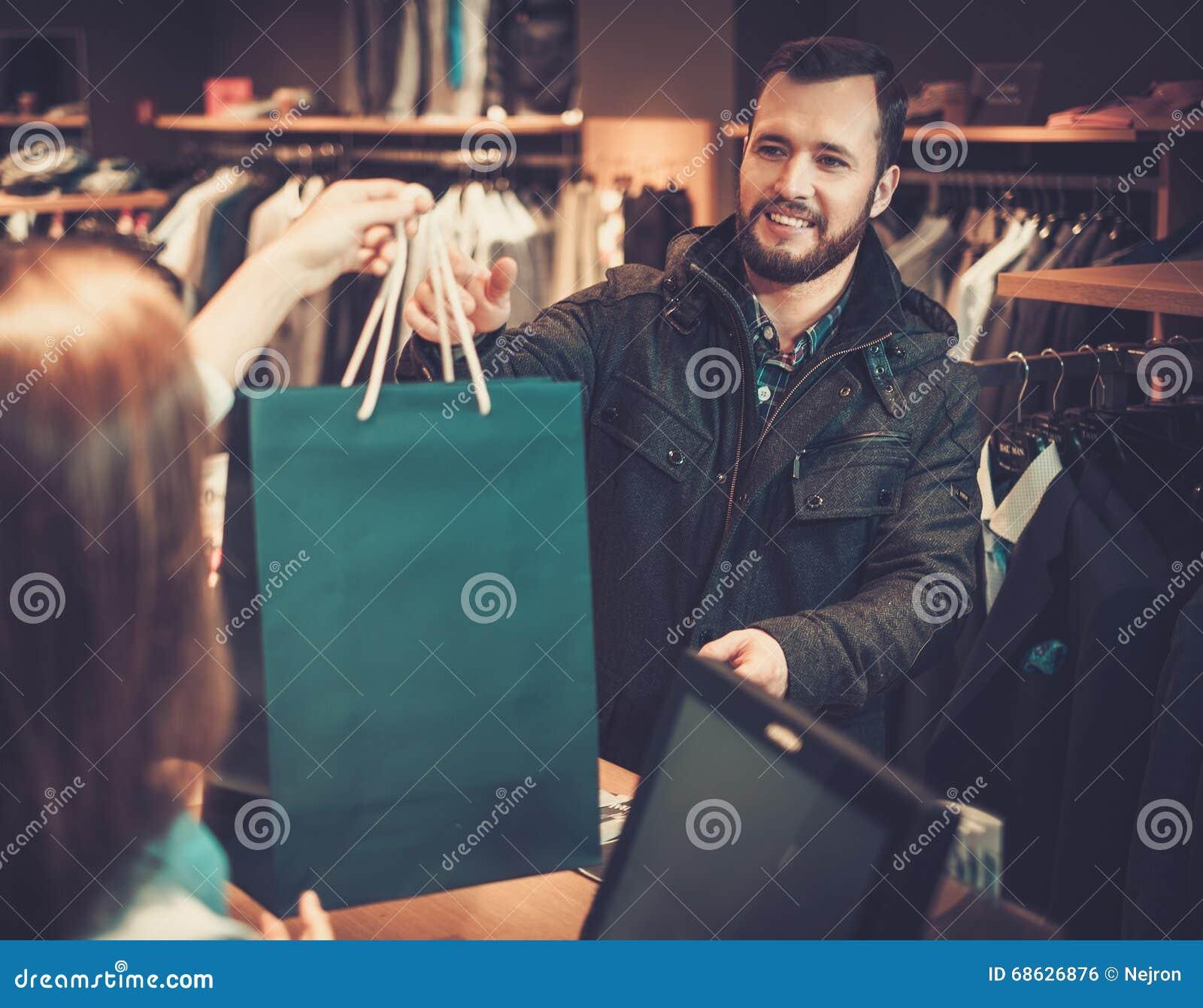 95674b55a48598 Szczęśliwi przystojni mężczyzna bierze torba na zakupy od sprzedawczyni w  kostiumu sklepie