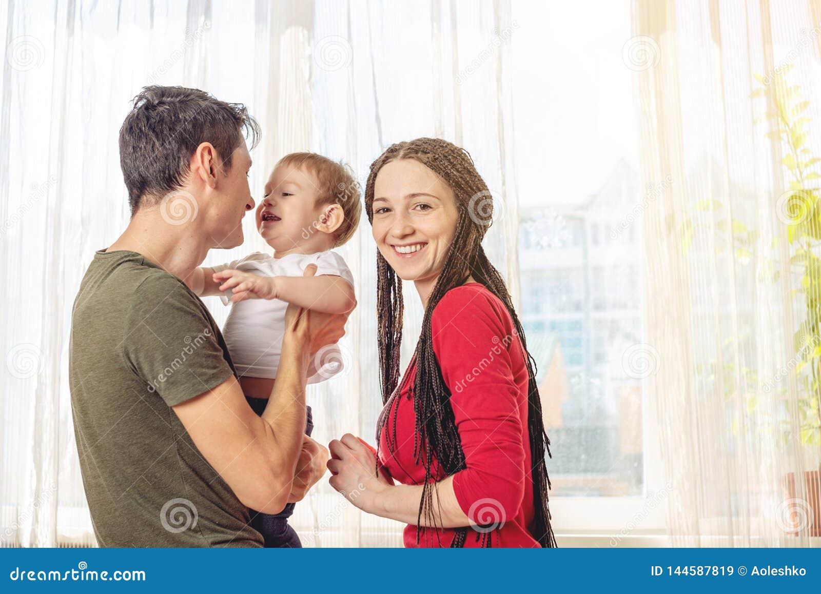 Szczęśliwy rodzica ojciec i matka bawić się z dziecko synem przy dalej nadokiennym tłem Rozochocona i nowożytna młoda rodz