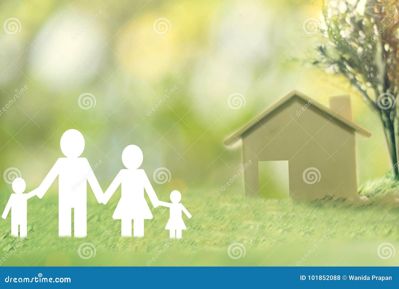 Szczęśliwy rodzina papier na zielonej trawie widzii dom dla ratować pieniądze sprzedaż