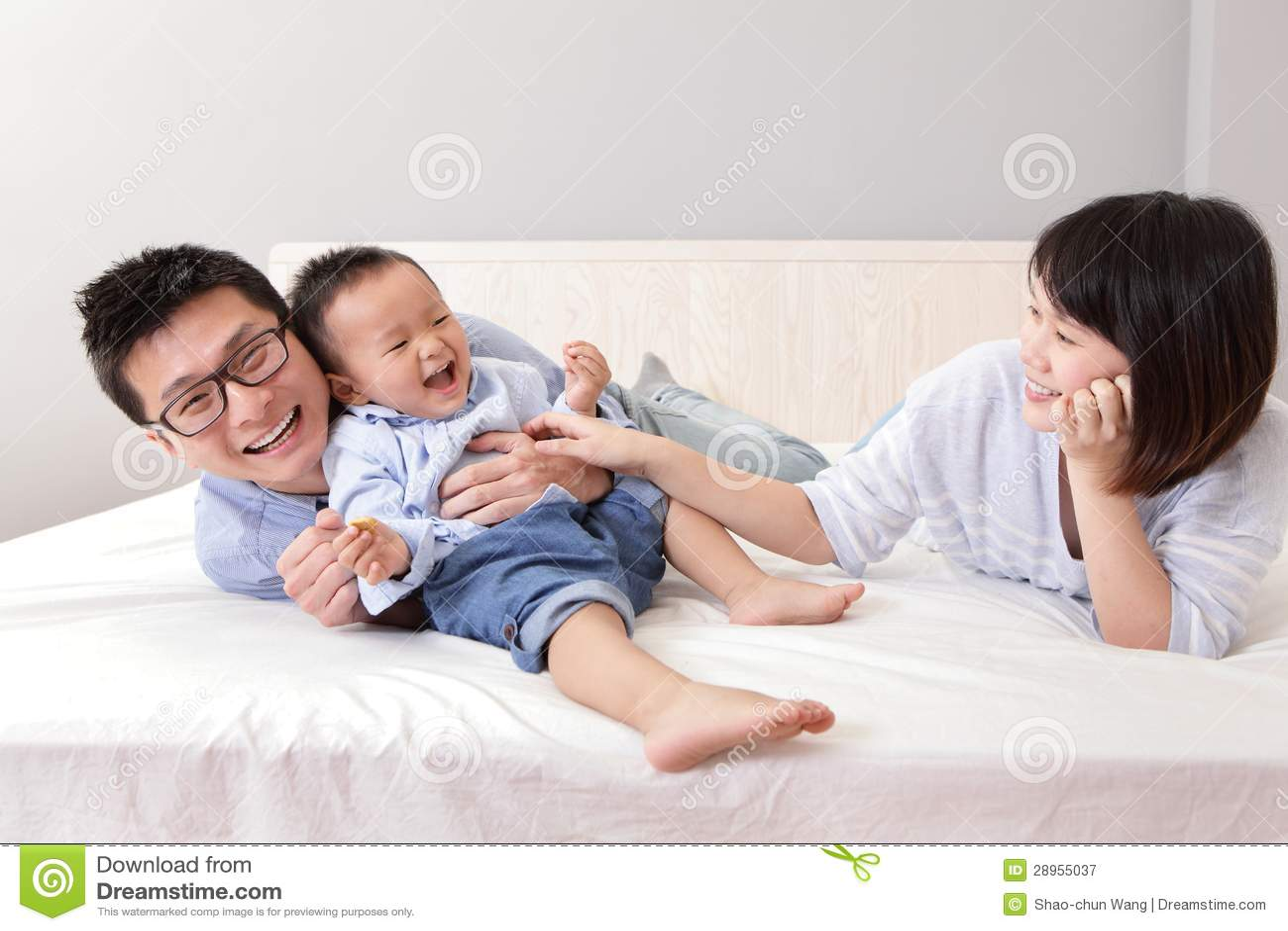 Szczęśliwy rodzinny bawić się na białym łóżku