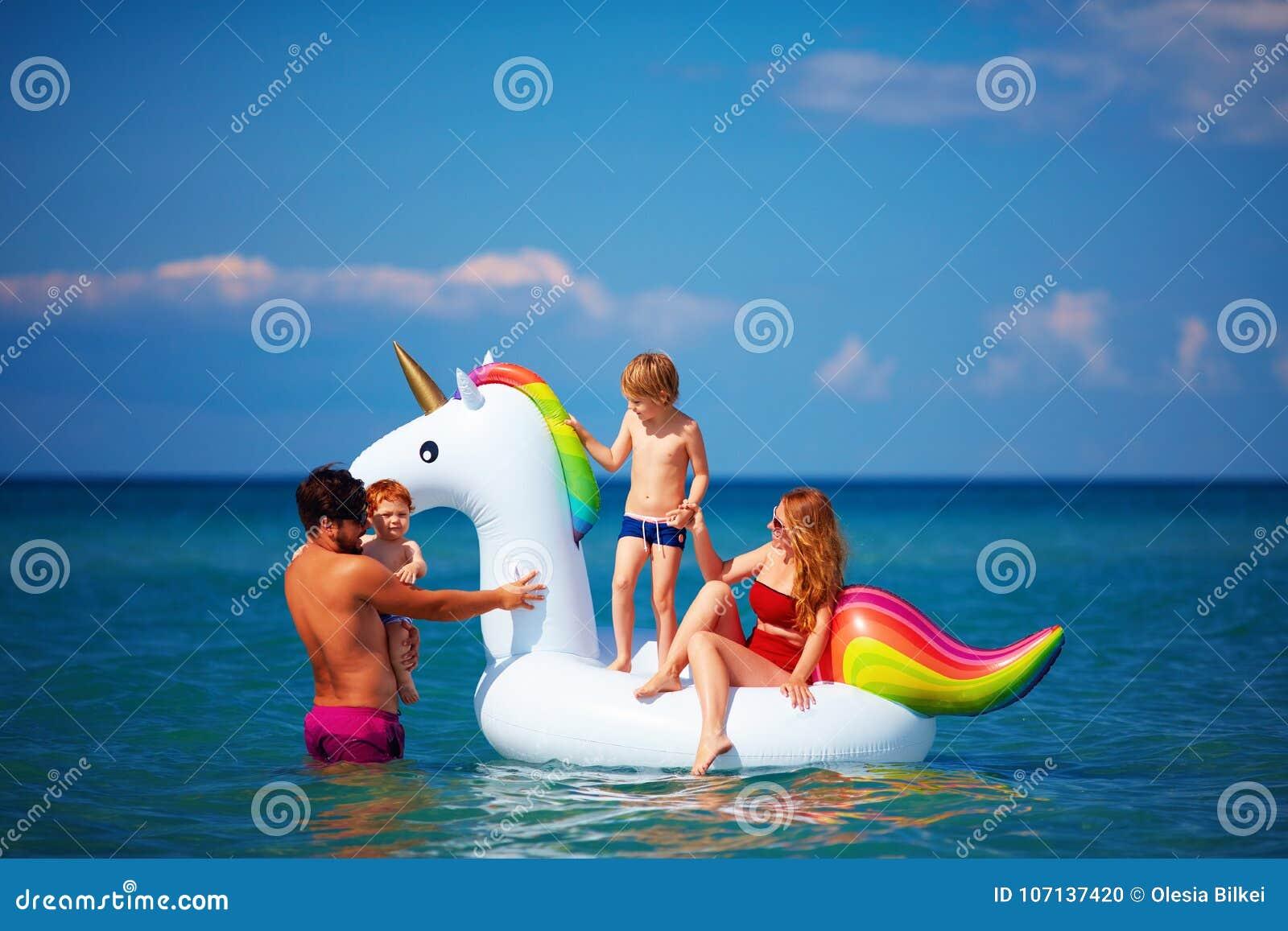 Szczęśliwy rodzinny cieszy się wakacje, mieć zabawę w wodzie na nadmuchiwanej jednorożec