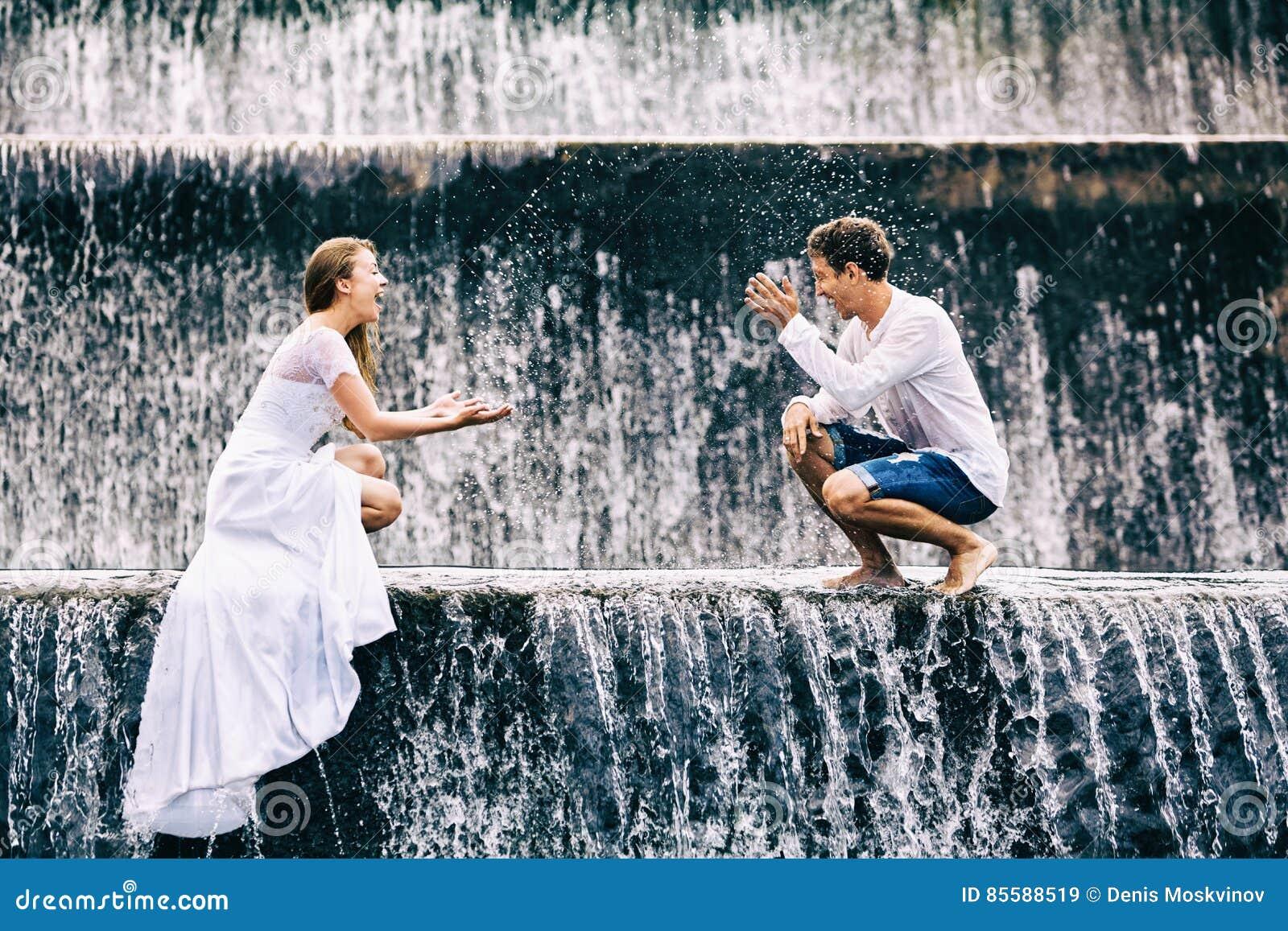 Szczęśliwy rodzinny miesiąca miodowego wakacje Para w kaskadowym siklawa basenie
