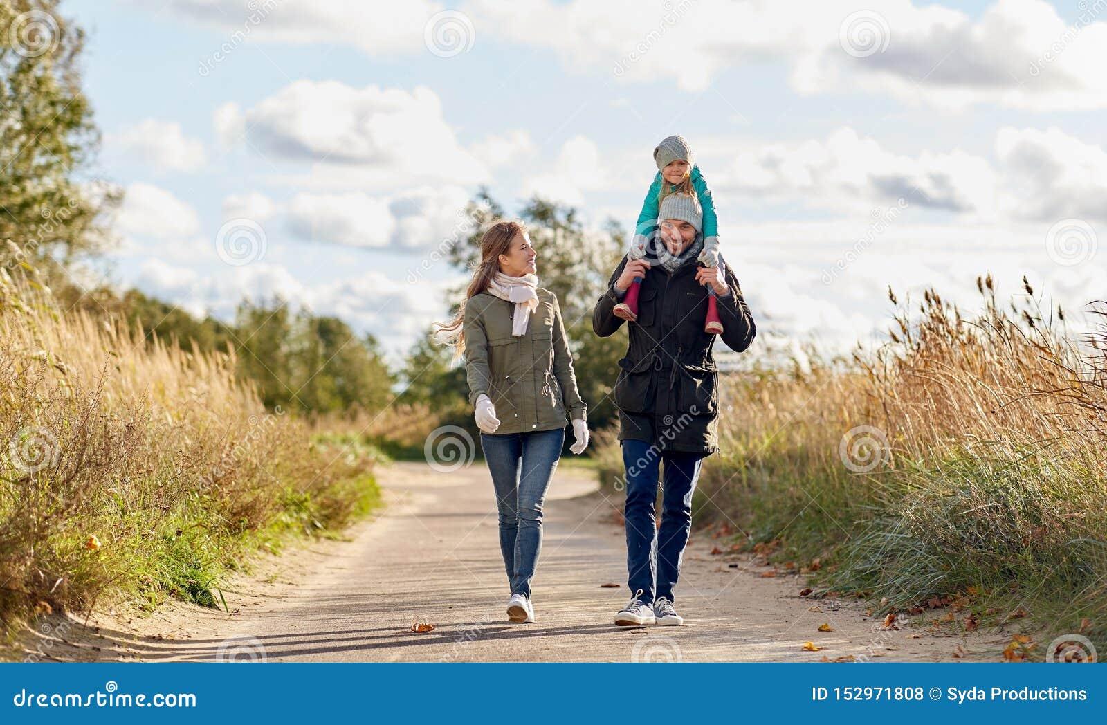 Szczęśliwy rodzinny odprowadzenie wzdłuż jesieni drogi