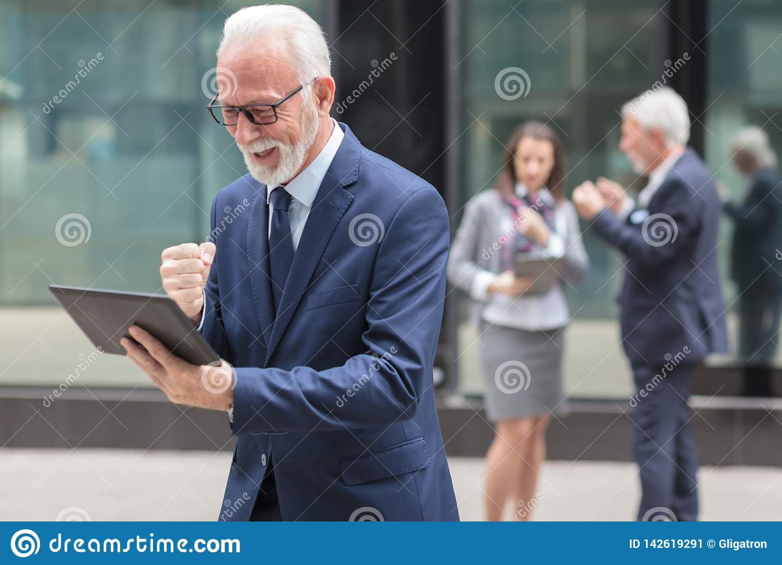 Szczęśliwy starszy biznesmen używa pastylkę, stoi przed budynkiem biurowym