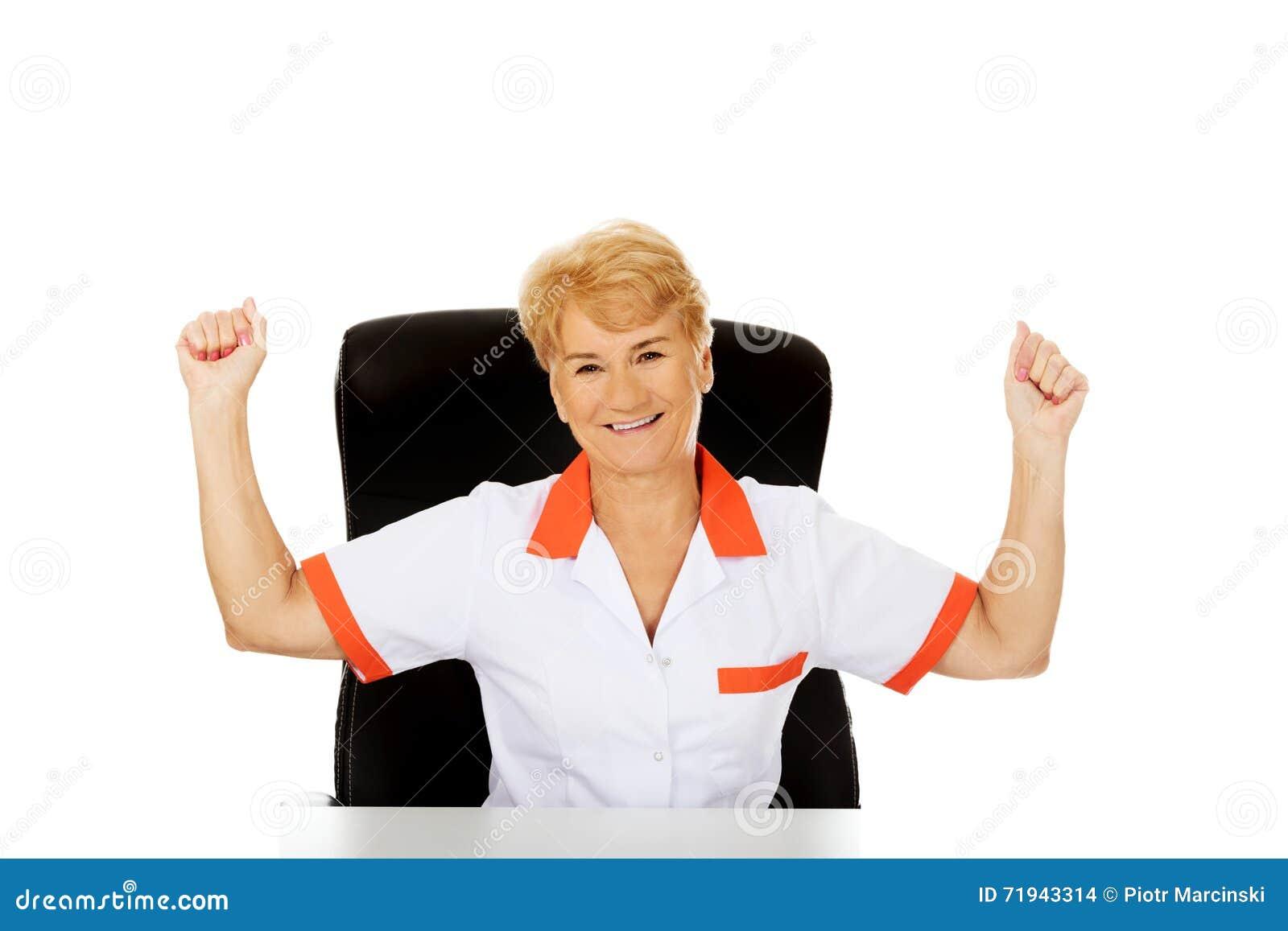 Szczęśliwy starszy kobiety pielęgniarki lub lekarki obsiadanie za biurka withd wręcza up