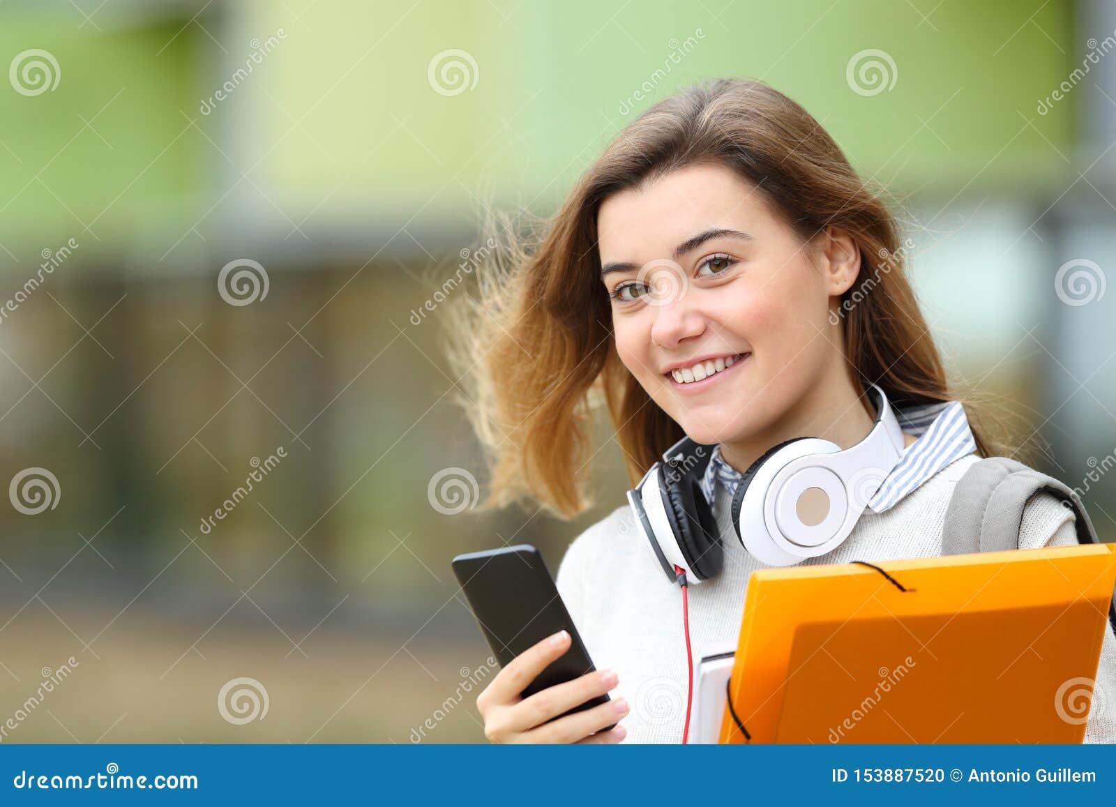 Szczęśliwy studencki pozować z hełmofonami i telefonem