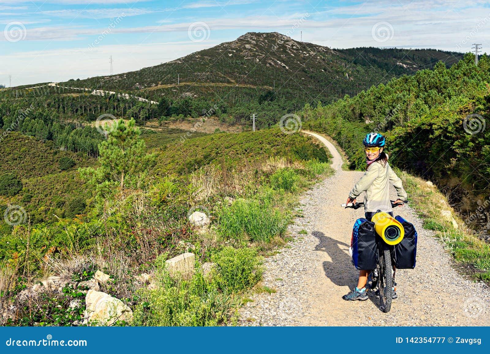 Szczęśliwy turystyczny cyklista na kamienistej górkowatej drodze