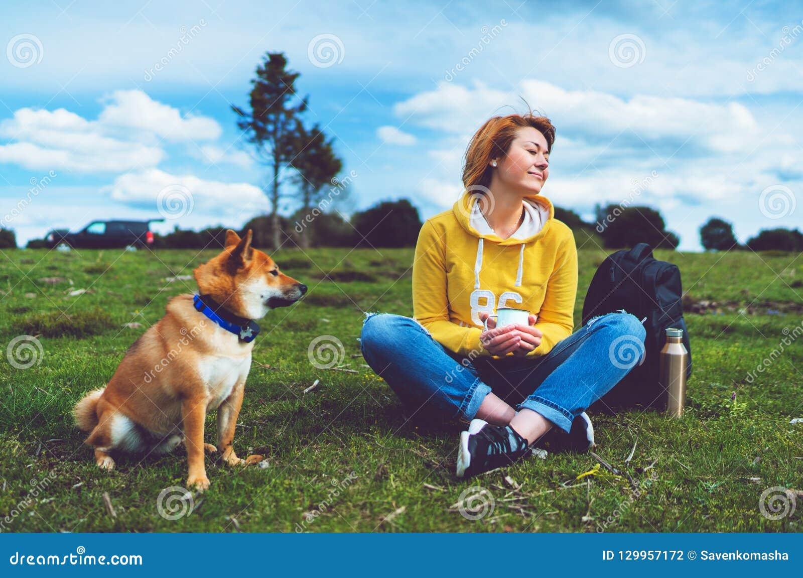Szczęśliwy uśmiech dziewczyny mienie w ręki filiżanki napoju, czerwony japończyka psa shiba inu na zielonej trawie w outdoors nat