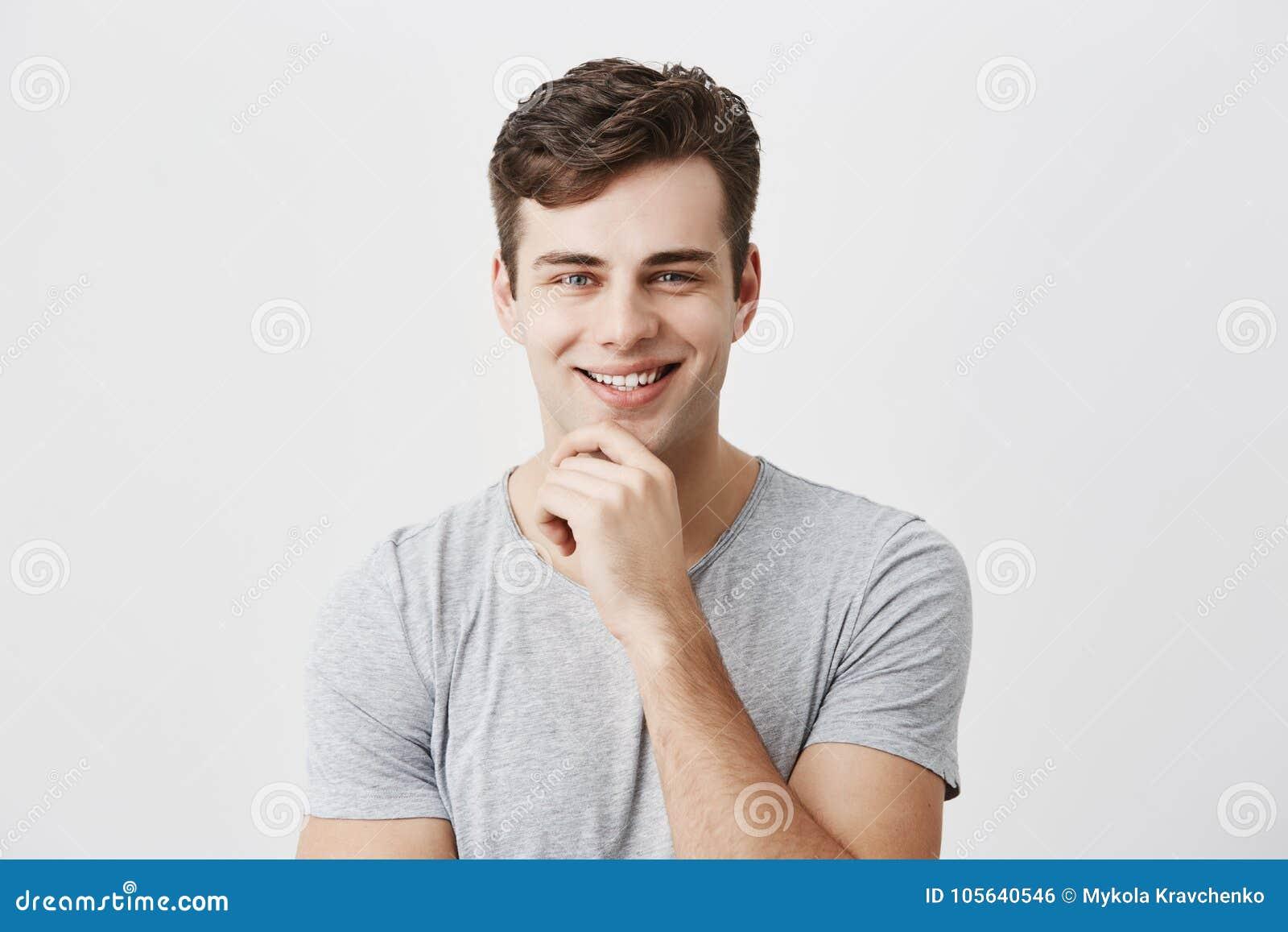 Szczęśliwy uśmiechnięty młody człowiek demonstruje pozytywne emocje lub uczucia, modnego uczesanie, ubierającego niezobowiązująco