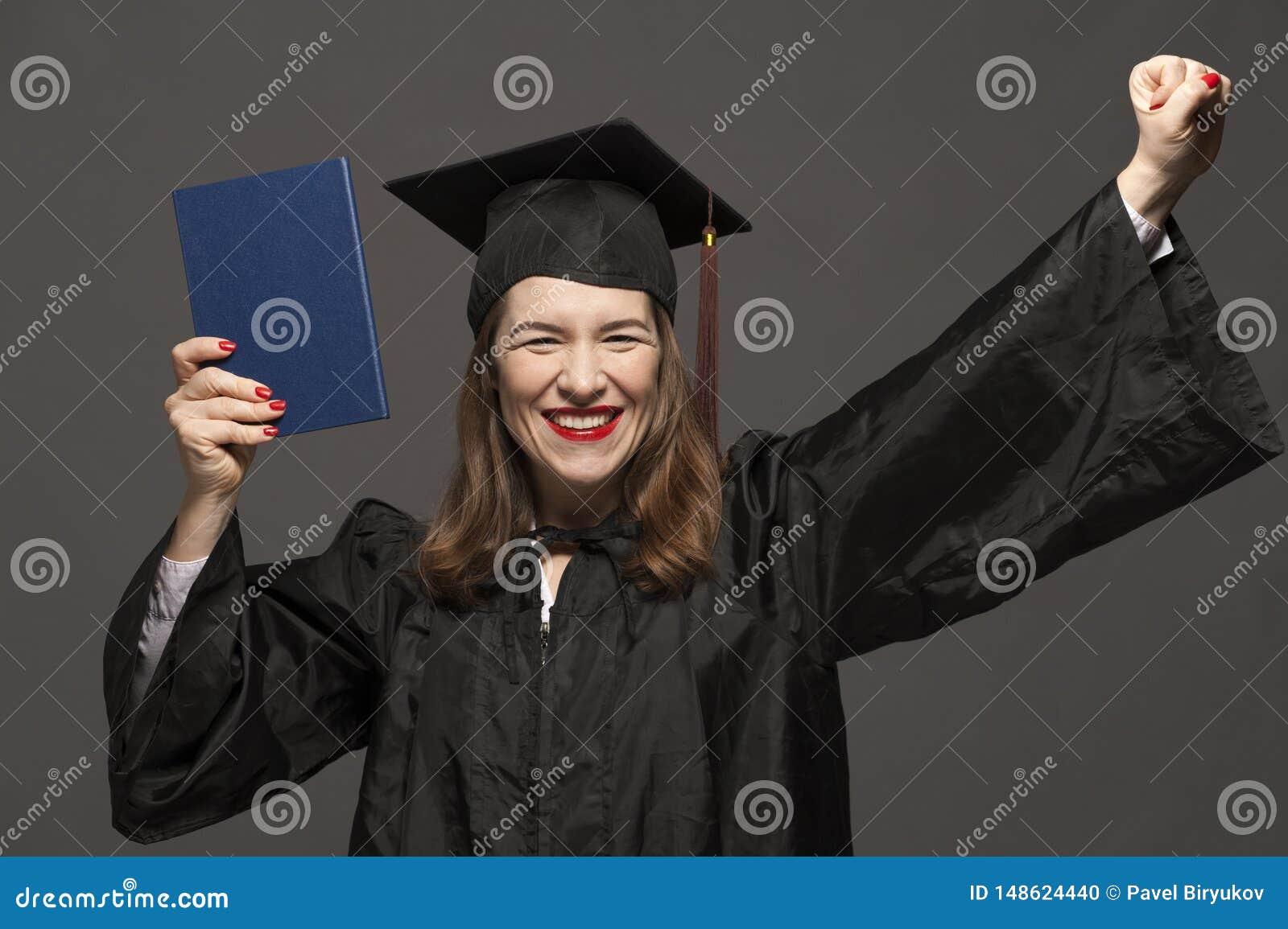 Szczęśliwy uśmiechnięty magisterski żeński uczeń jest ubranym czarnego mortarboard i salopę z ściernią w eyeglasses