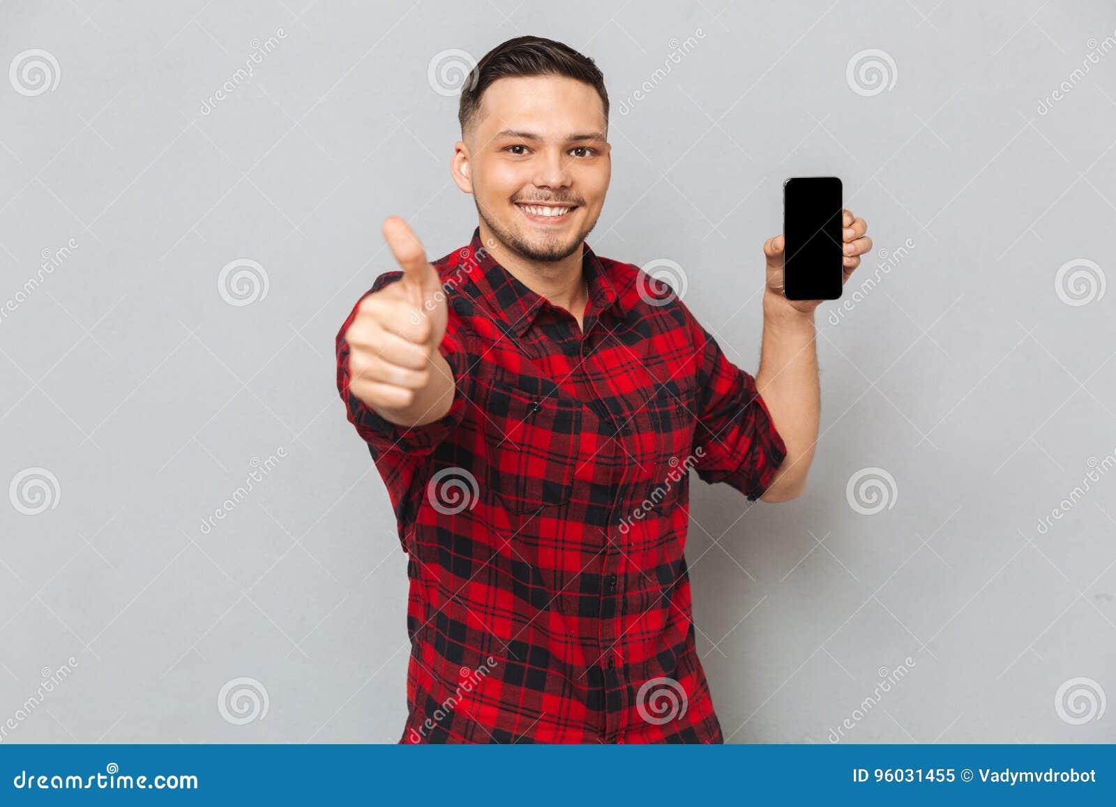 Szczęśliwy uśmiechnięty przypadkowy mężczyzna trzyma pustego ekranu telefon komórkowego