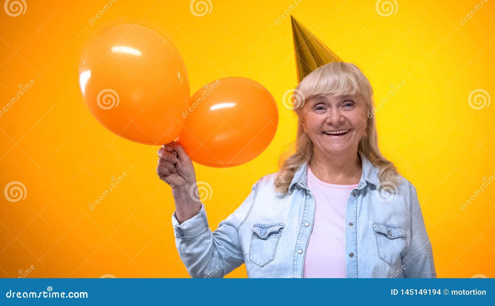Szczęśliwy uśmiechnięty starszy damy mienie szybko się zwiększać na żółtym tle, rocznica