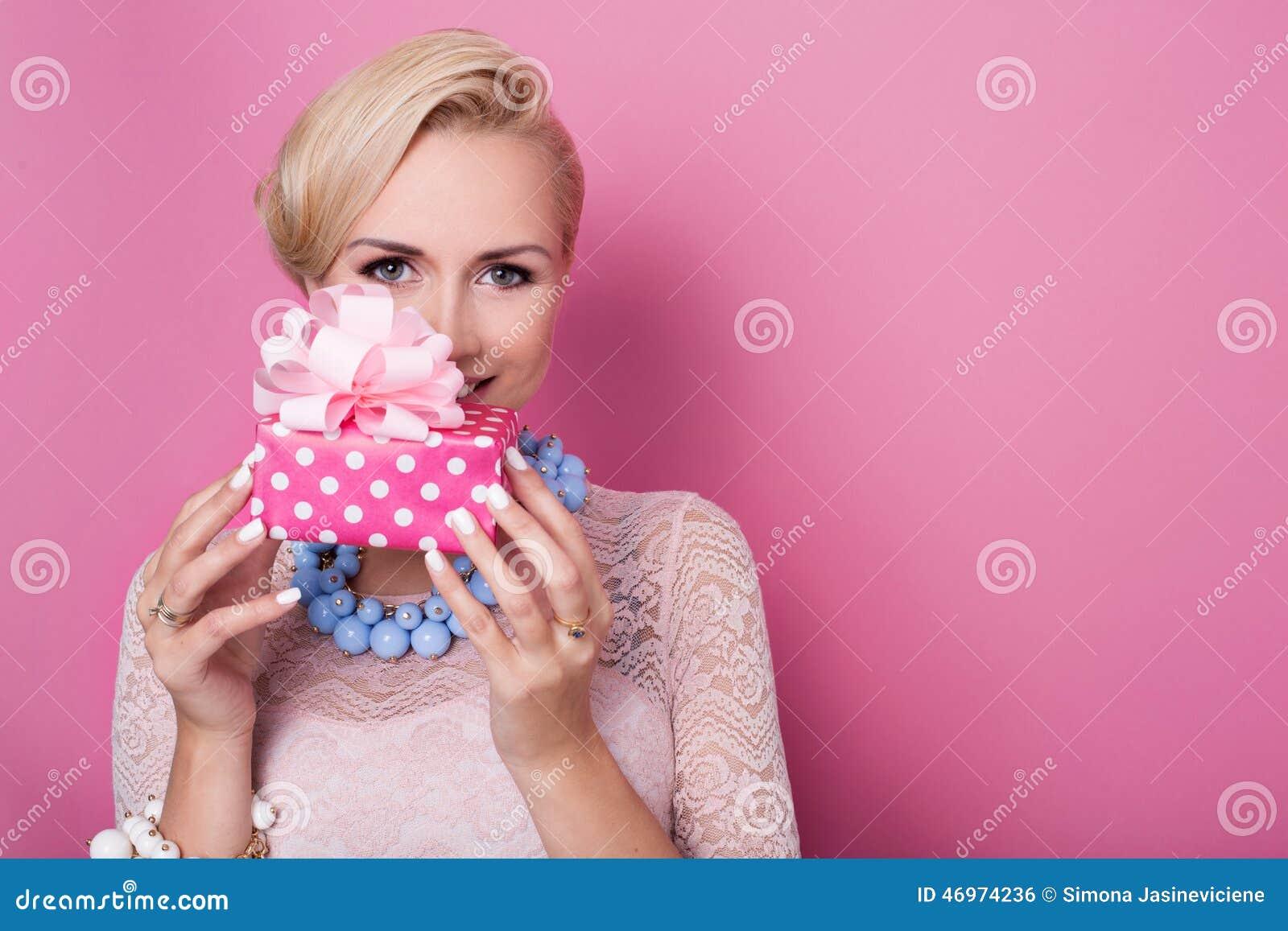 Szczęśliwy urodziny Słodka blondynki kobieta trzyma małego prezenta pudełko z faborkiem kolorów strzałek głębii pola płycizny mię
