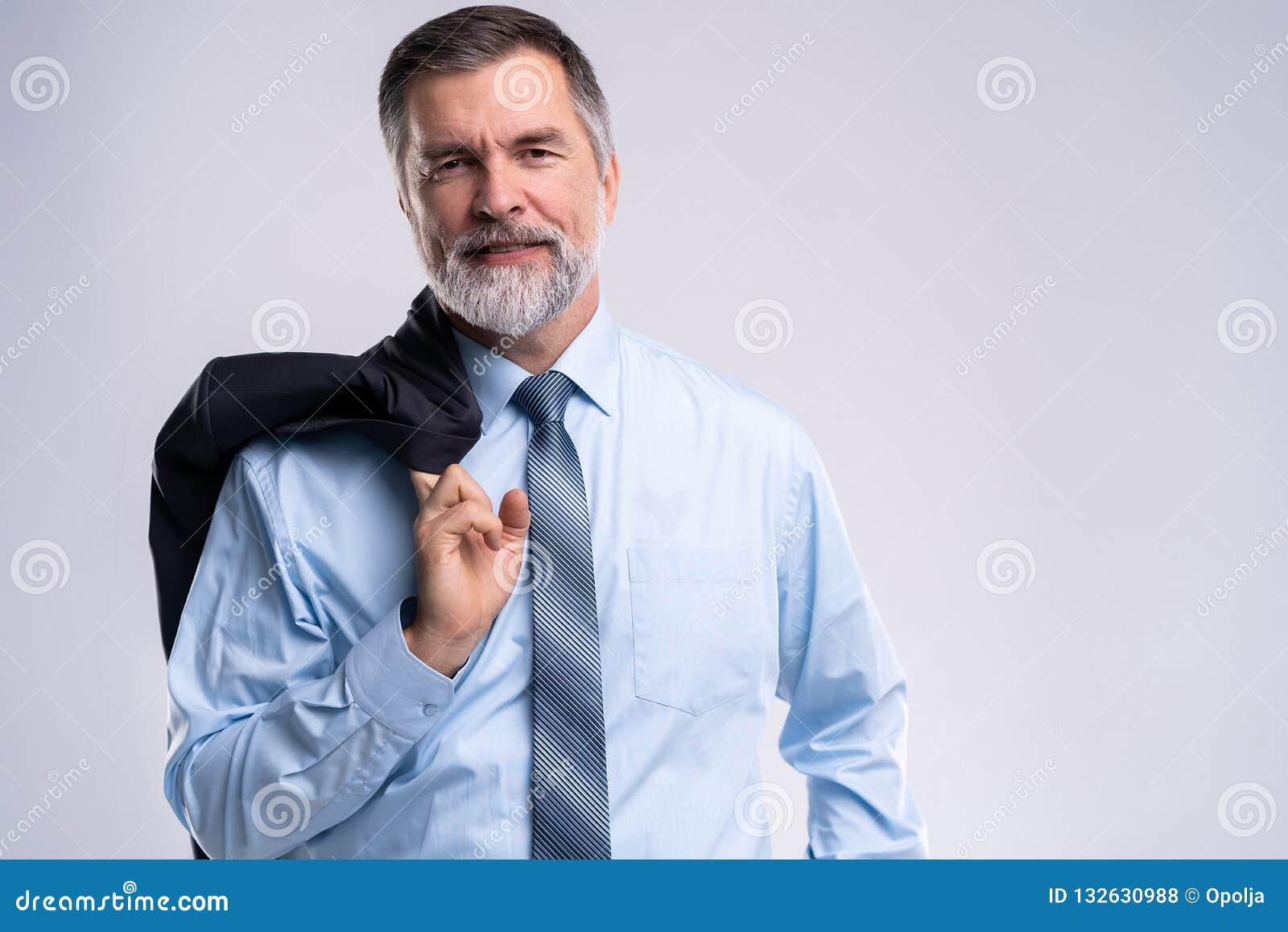 Szczęśliwy zadowolony dojrzały biznesmen patrzeje kamerę odizolowywającą na białym tle