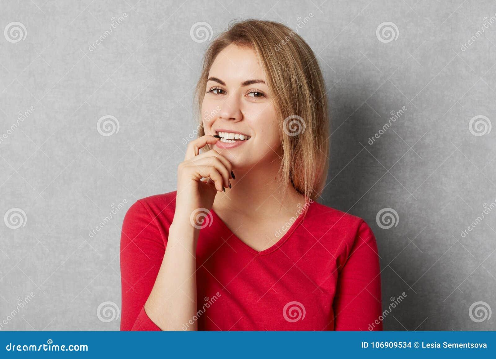 Szczęśliwy zadowolony kobieta model ubierał w czerwieni ubraniach, spojrzenia z ufnym wyrażeniem nad popielatym tłem, modele w st
