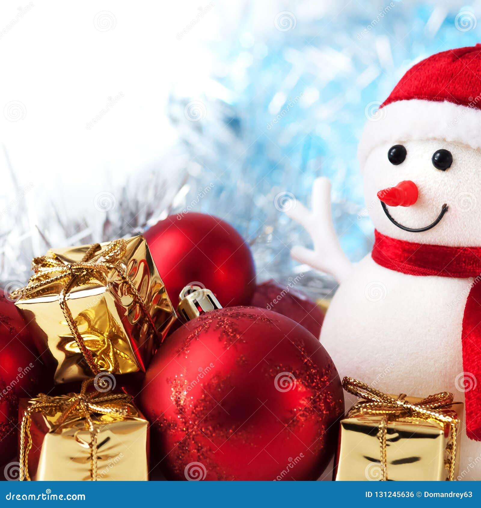 Szczęśliwych Świąt Bożego Narodzenia, nowy rok, bałwan, prezenty w złotych pudełkach i czerwone piłki na bokeh tle, błękitnym i b
