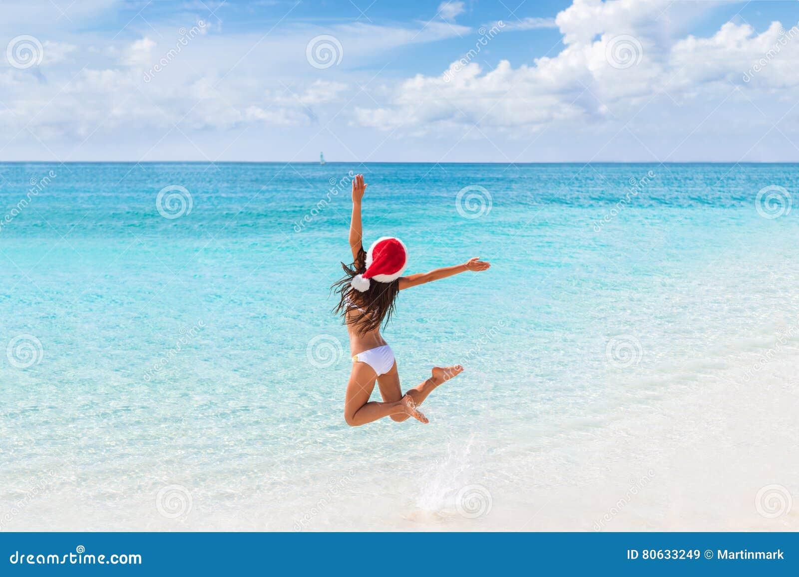 Szczęśliwych bożych narodzeń dziewczyny kapeluszowy doskakiwanie radość na plaży