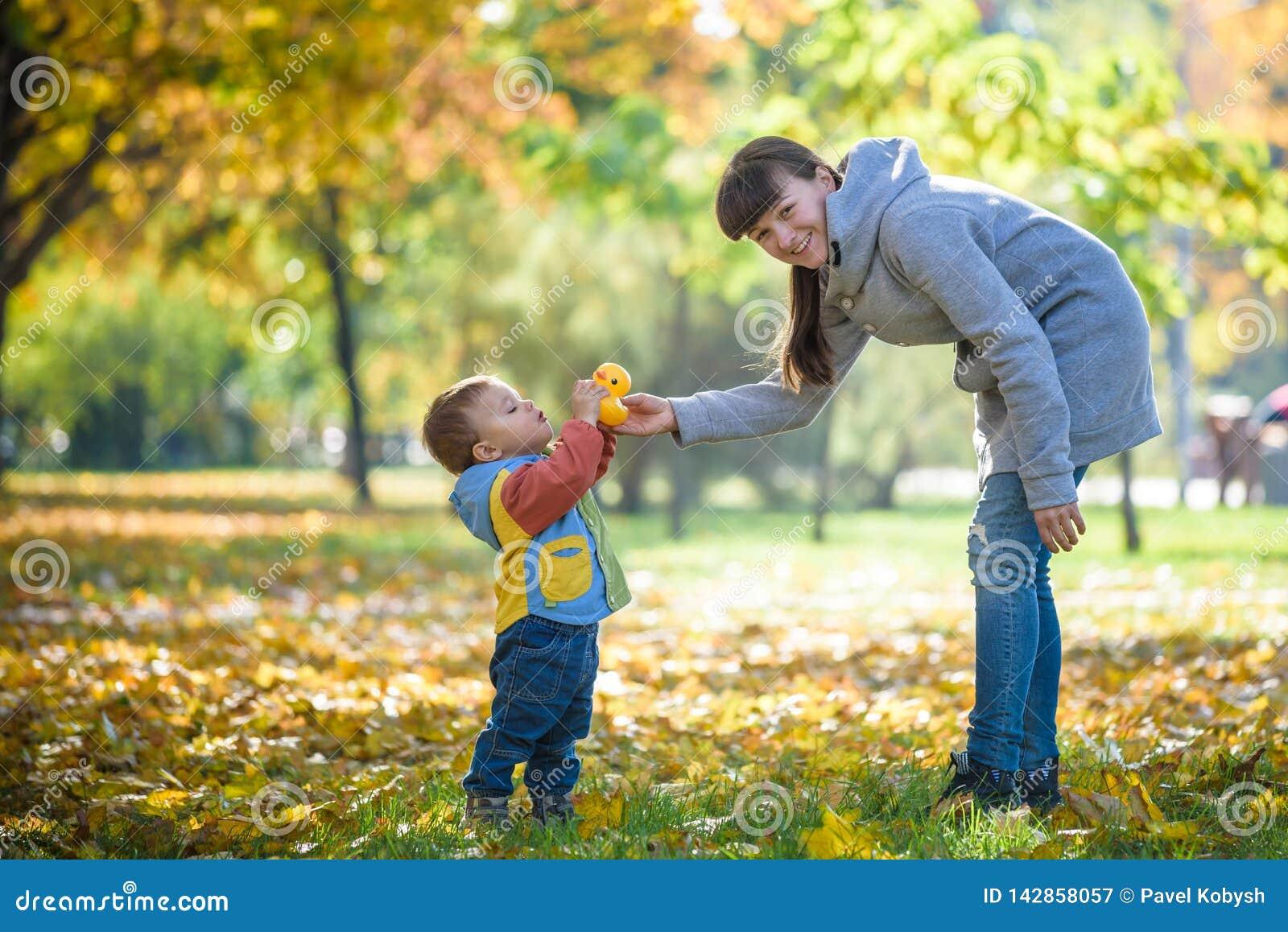 Szczęśliwych potomstw macierzysty bawić się z dzieckiem w jesień parku z żółtymi liśćmi klonowymi Rodzinny odprowadzenie outdoors