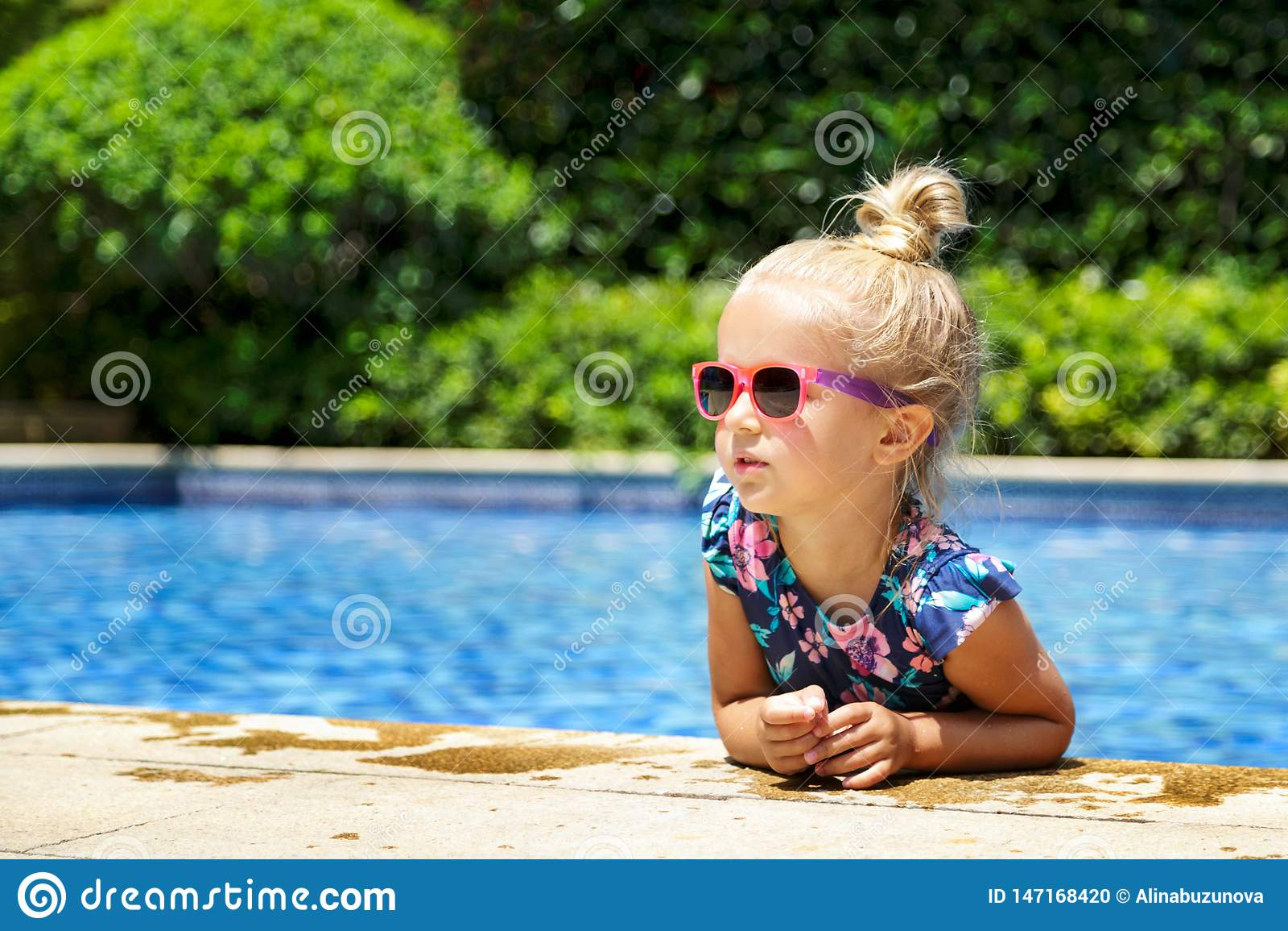Szcz??liwa ma?a dziewczynka w plenerowym basenie na gor?cym letnim dniu Dzieciaki ucz? si? p?ywa? Dziecko sztuka w tropikalnym ku