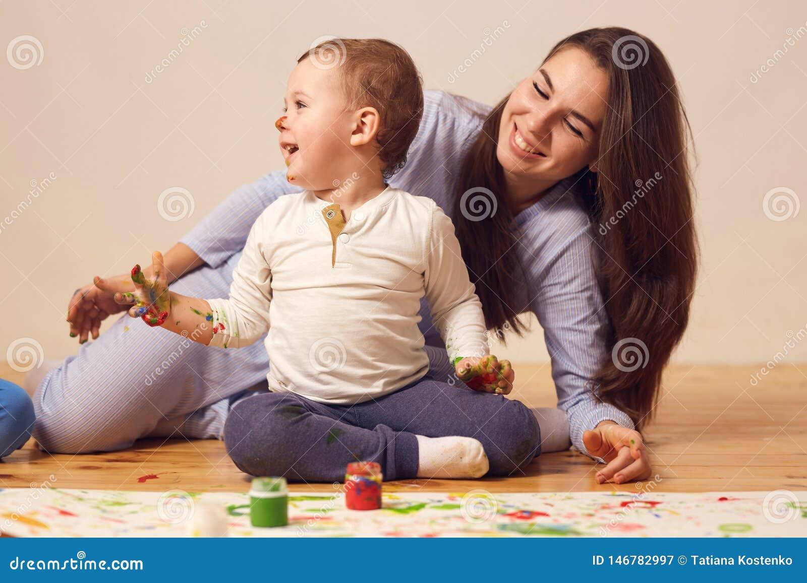 Szcz??liwa matka i jej ma?y syn z farbami na jego twarzy ubieraj?cej w dom?w ubraniach siedzimy na drewnianej pod?odze w