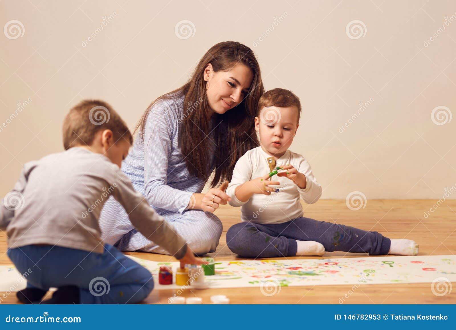 Szcz??liwa potomstwo matka i jej dwa ma?ego syna ubieraj?cych w dom?w ubraniach siedzimy na drewnianej pod?odze w pokoju i