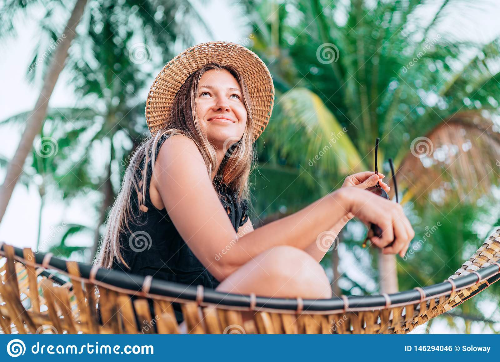 Szcz??liwa u?miechni?ta m?oda kobieta w s?omianego kapeluszu obsiadaniu w hamaku z drzewka palmowego t?em