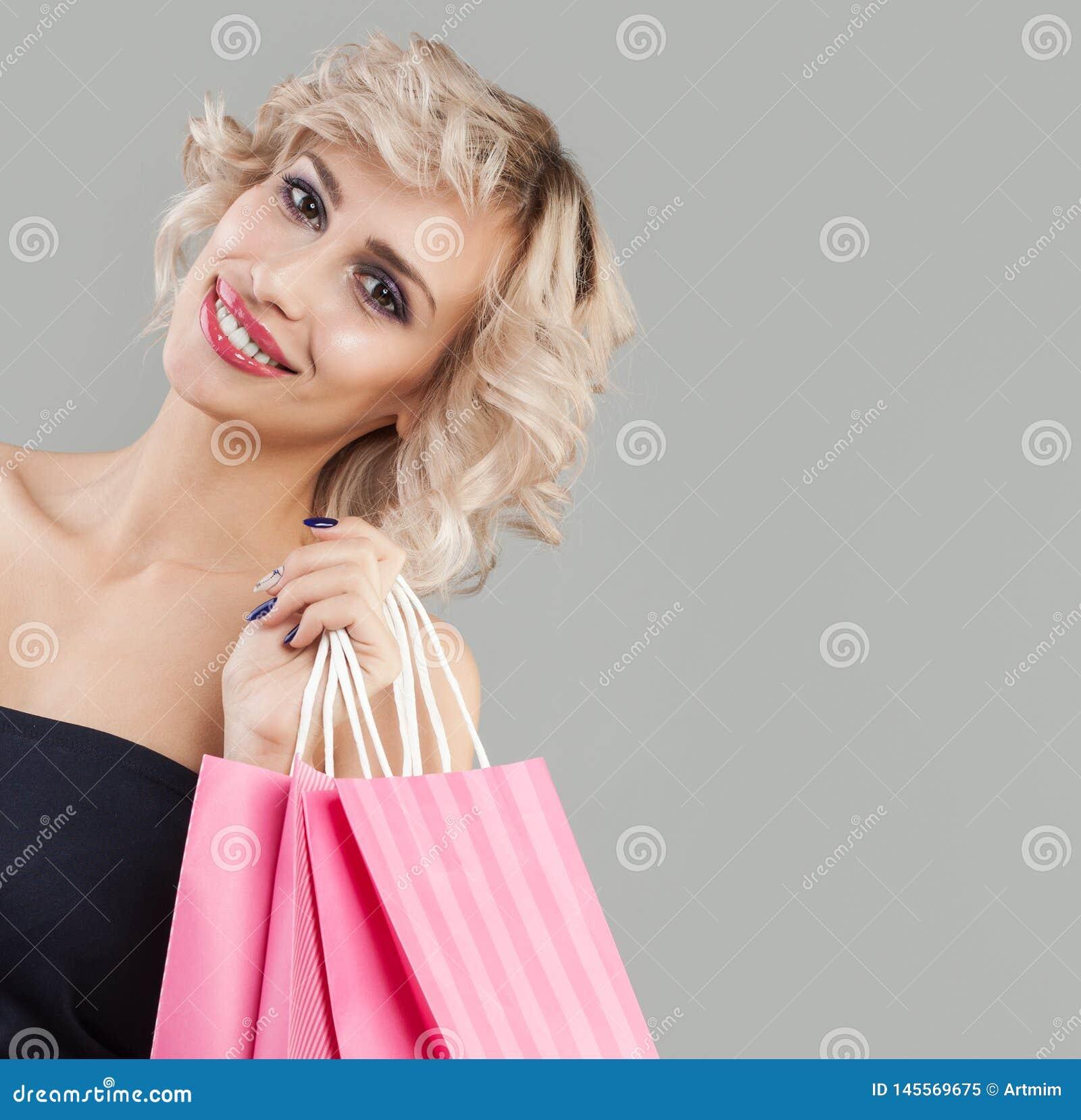 Szcz??liwego portreta u?miechni?ta kobieta Śliczny model z różowymi torbami na zakupy