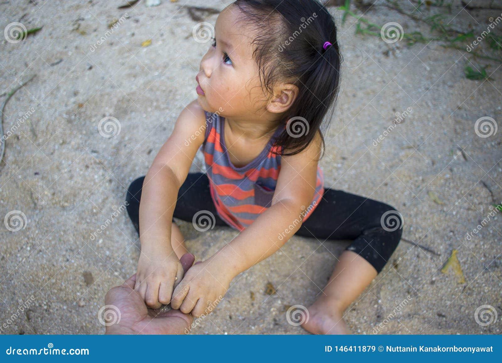 Szcz??liwy dziecko bawi? si? z piaskiem, ?mieszna Azjatycka rodzina w parku