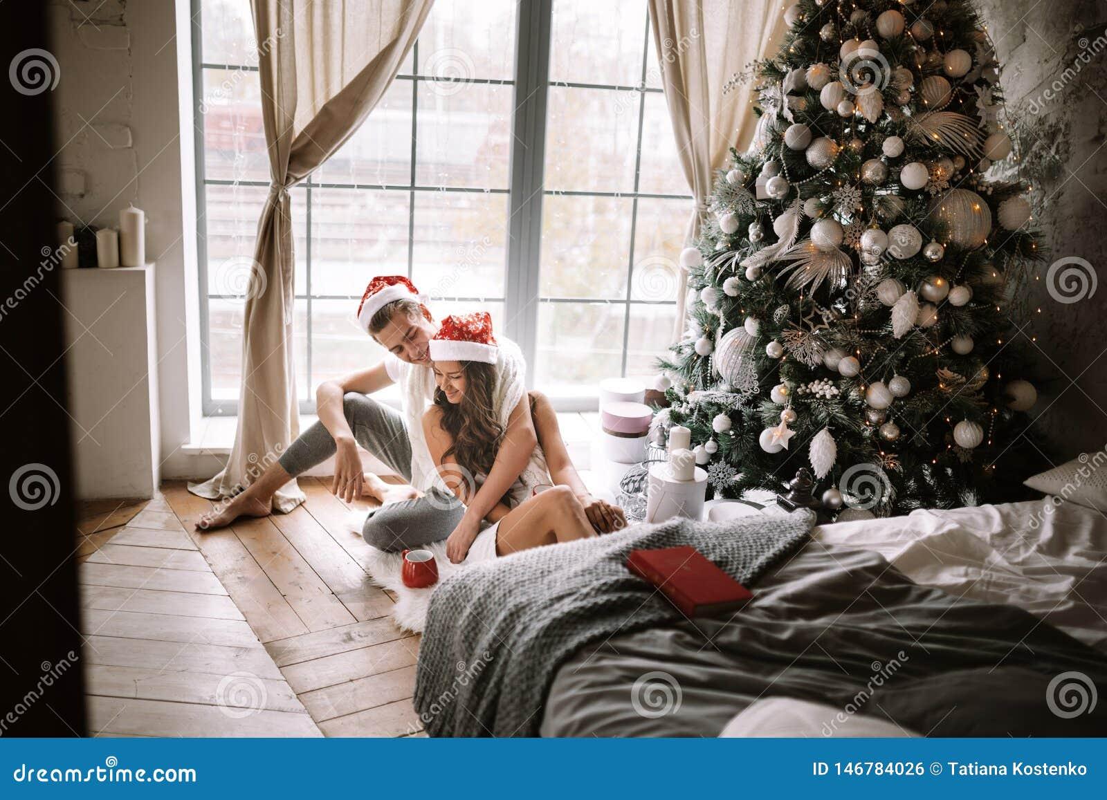 Szcz??liwy facet i dziewczyna w bia?ych ?wi?ty Miko?aj kapeluszach i koszulkach jeste?my siedz?cy i ?ciskaj?cy w pokoju na pod?od