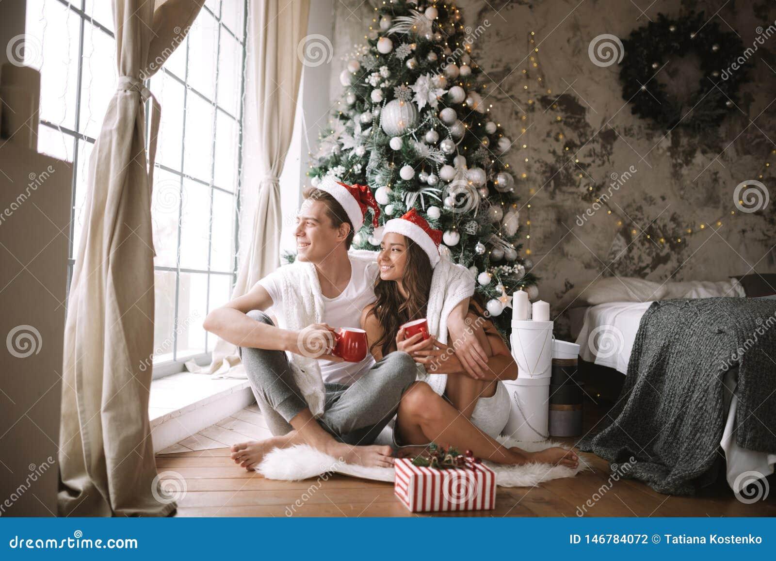 Szcz??liwy facet i dziewczyna w bia?ych ?wi?ty Miko?aj kapeluszach i koszulkach siedzimy z czerwonymi fili?ankami na pod?odze prz