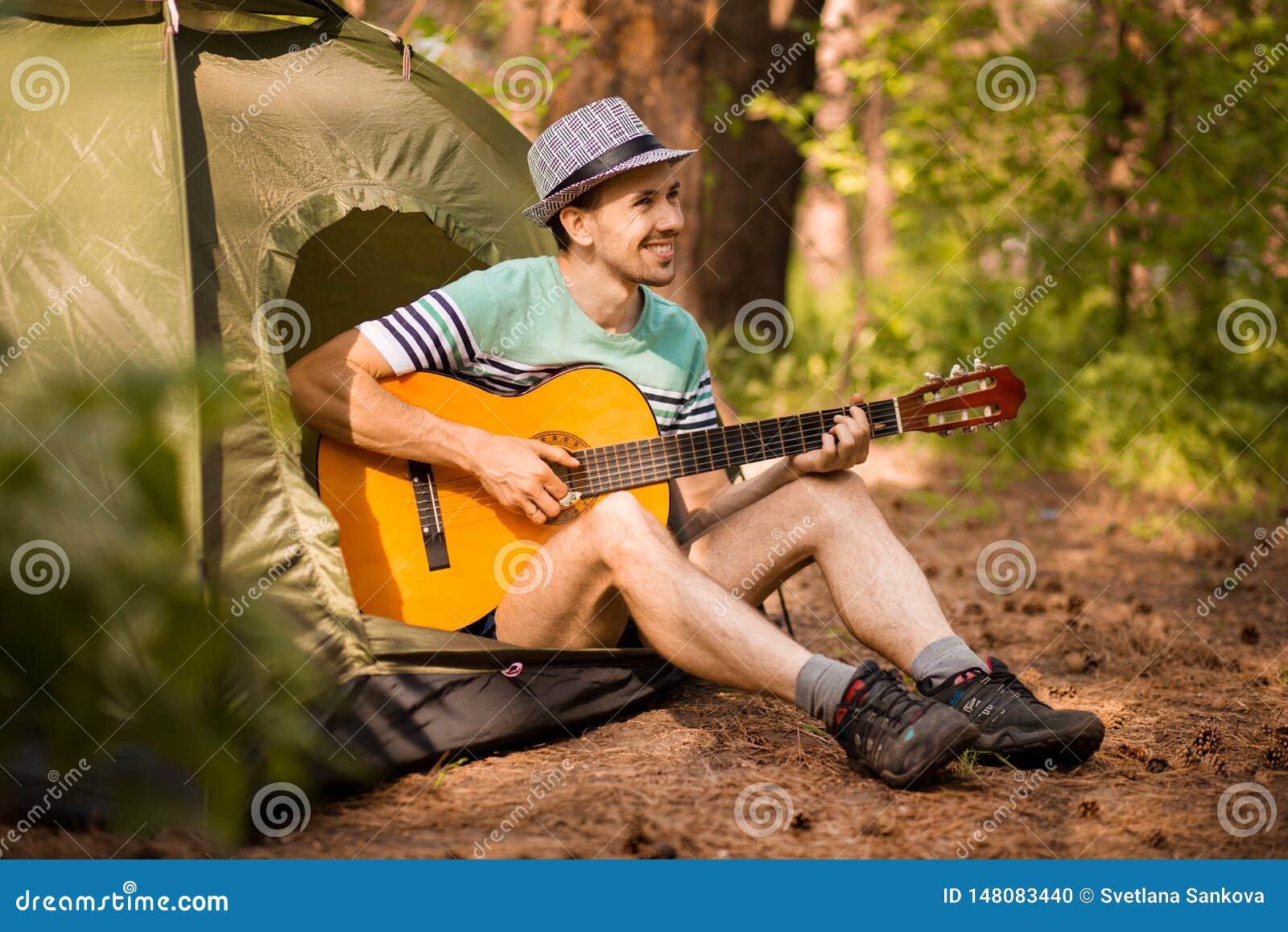 Szcz??liwy m?odego cz?owieka camping i pobrz?ka gitary instrumentaln? muzyk? relaksowa? przeciw t?u lasowy zmierzch