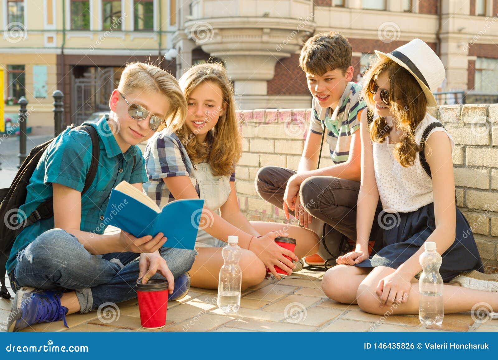 Szcz??liwy 4 nastoletniego przyjaciela lub szko?a ?rednia ucznie czyta telefon maj? zabaw?, opowiadaj?cy, ksi??ka Przyja?? i ludz
