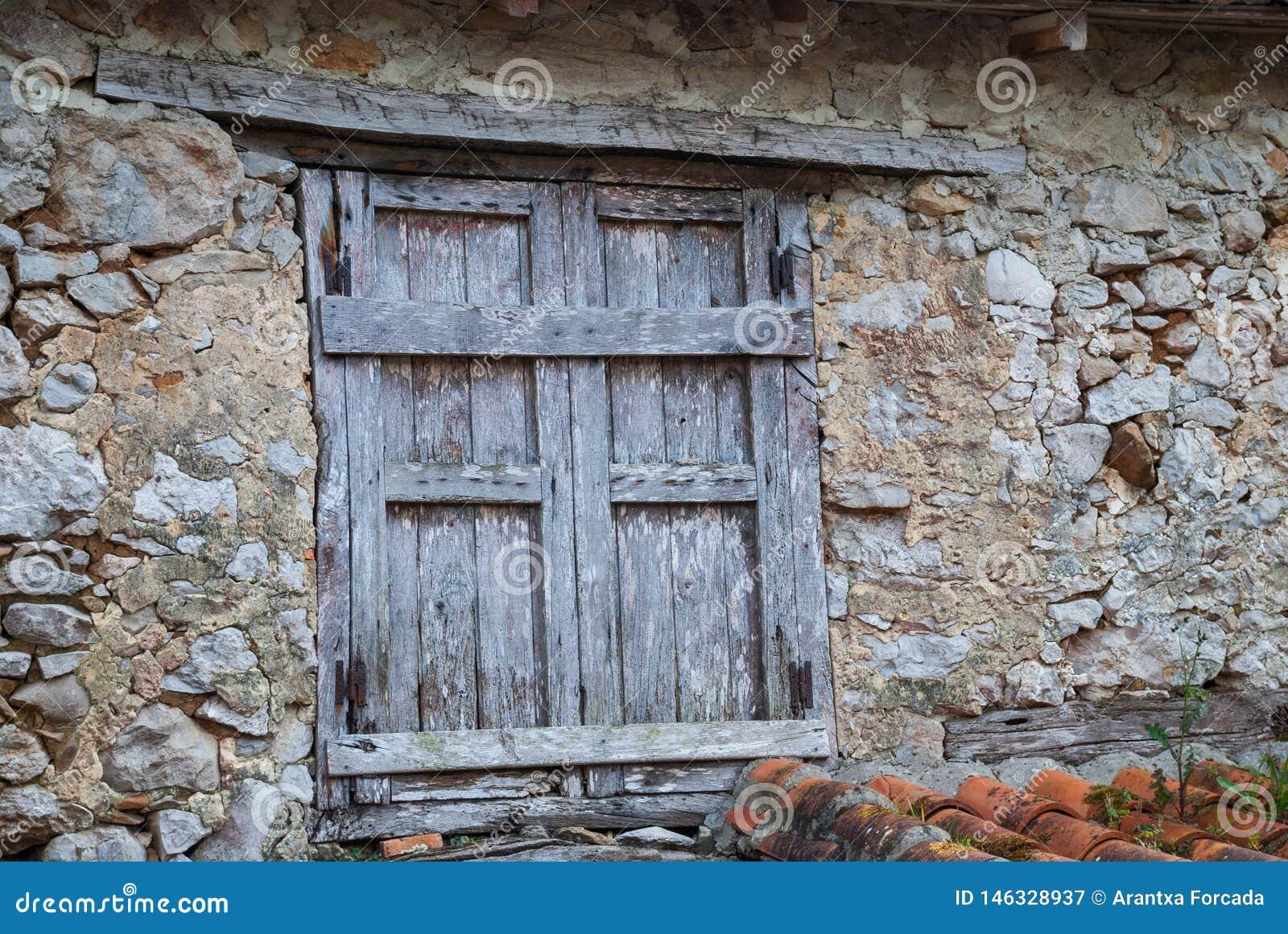 Szczegół drewniany okno w wyburzającym kamienia domu